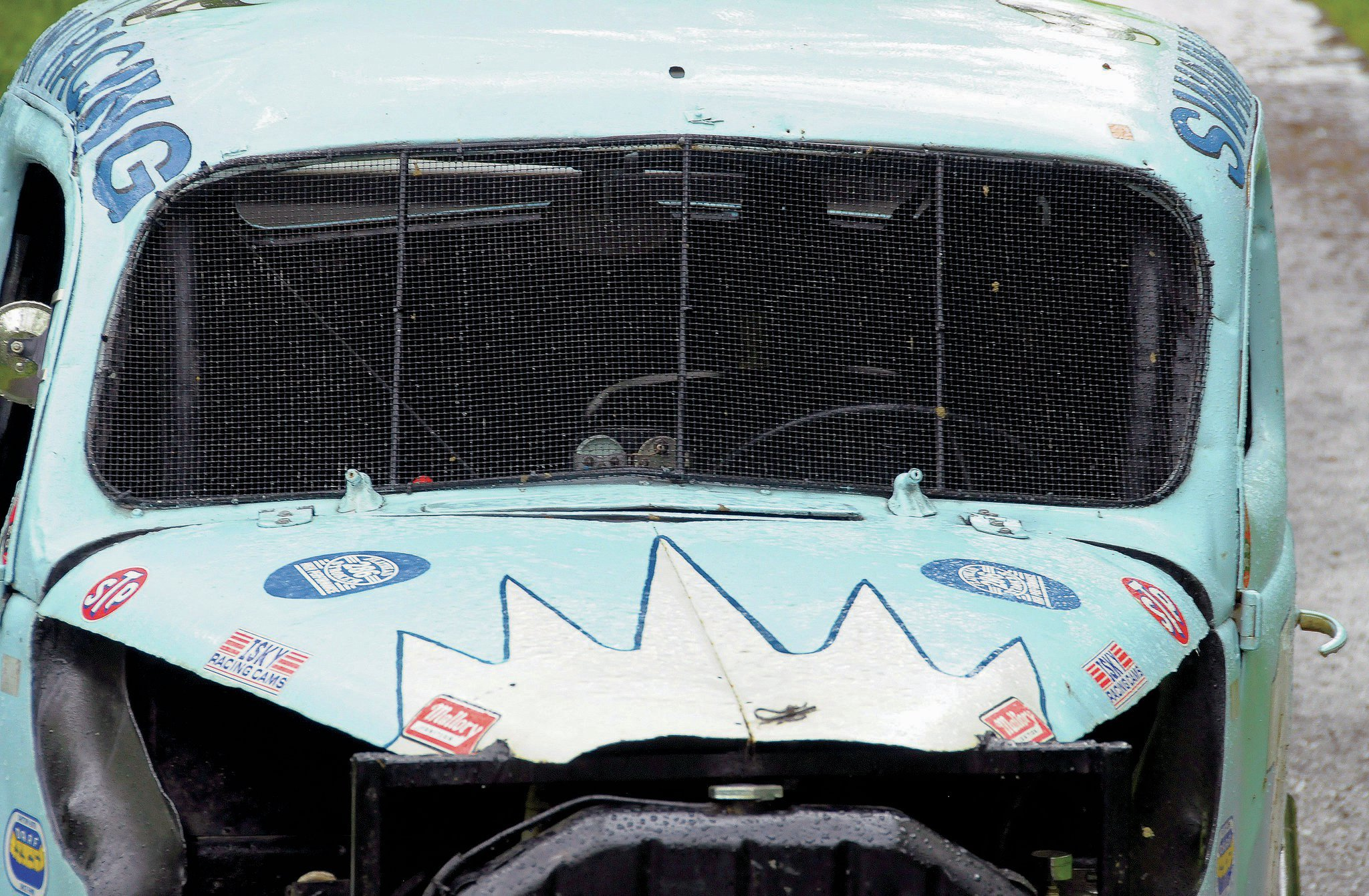 To contain inbound dirt clods and rocks, the windshield opening is covered by chicken wire. Look closely and you see that the wiper towers are still in position.