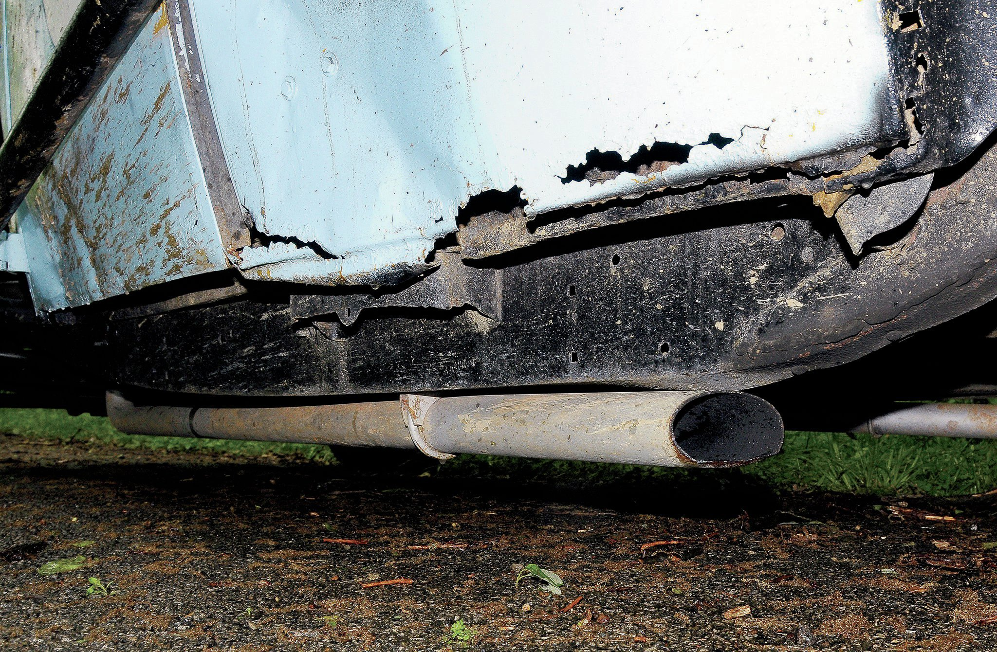 The exhaust pipes exited under the rear edge of the doors. A muffler clamp bolts it to the frame.