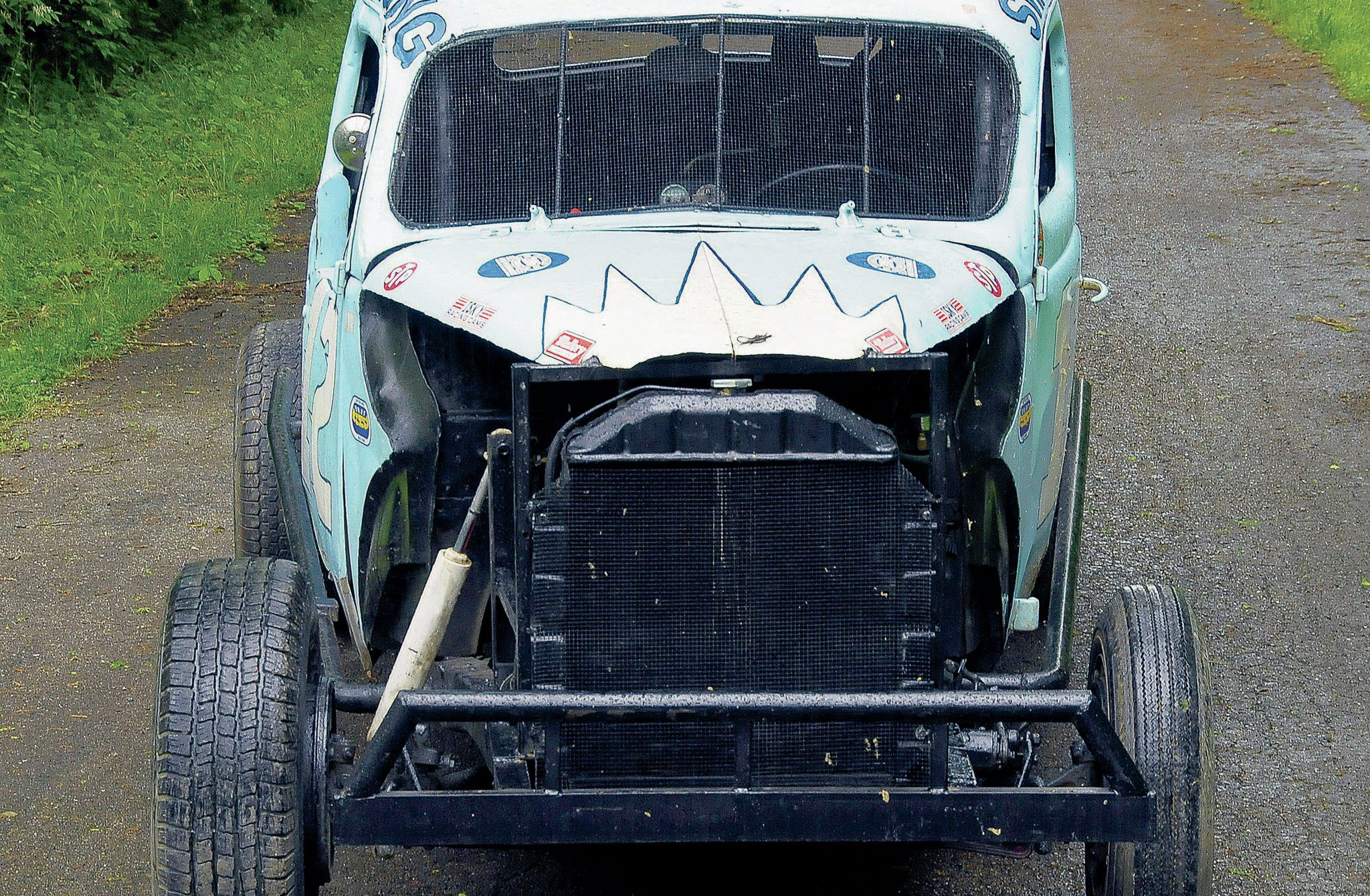 This head-on view of the car shows the larger right front tire. It along with the left front are both street tires while that sturdy front bumper was homemade of channel iron pipe, which made it great for pushing people out of the way. The larger right-side hydraulic shock is also visible.