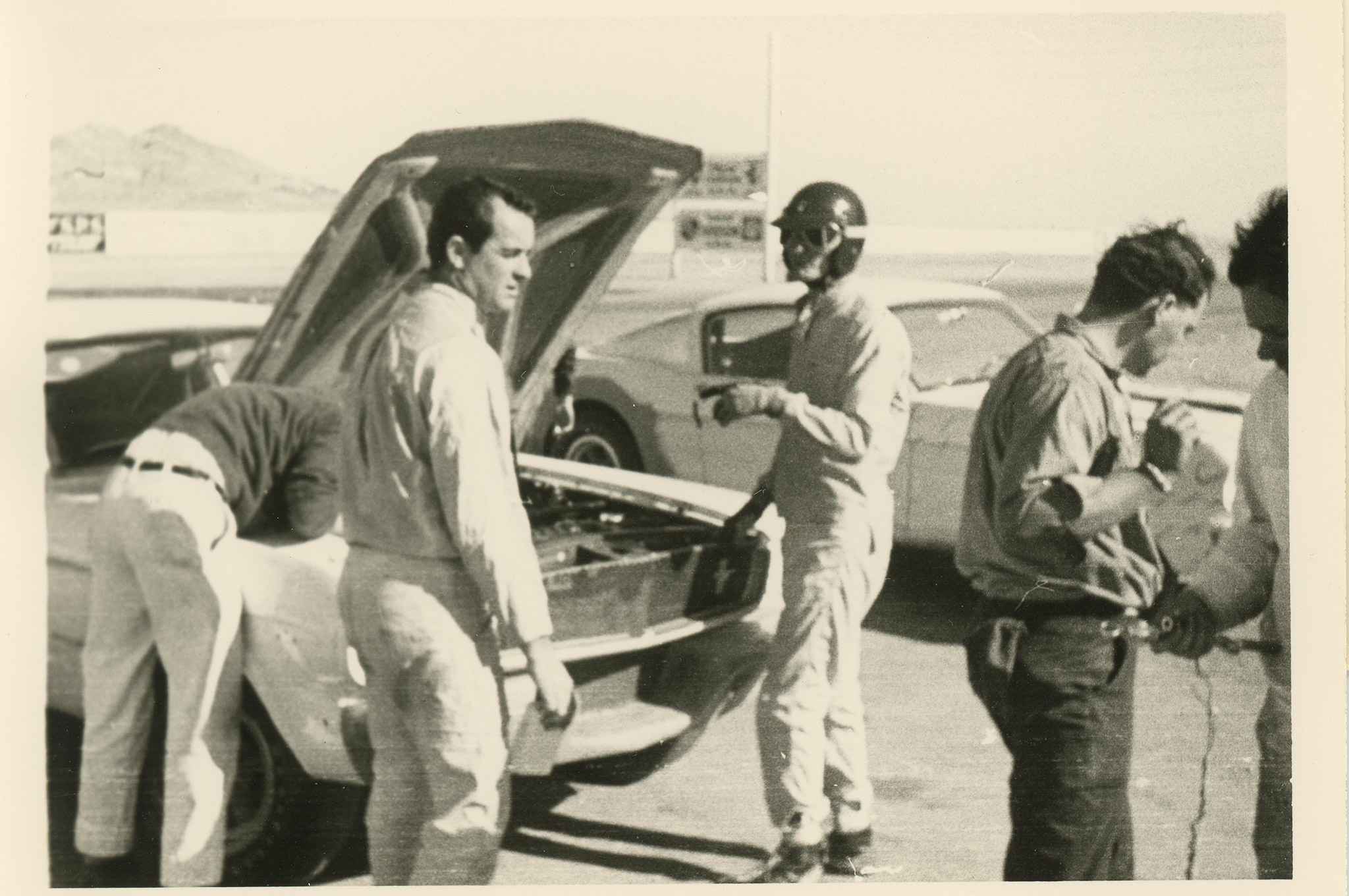 One month prior to the Green Valley, TX race, in January of 1965, Bob Bondurant and Ken Miles track tested the first two 1965 Shelby Mustangs at Willow Springs in California.  5R002 is in background, and 5R001, is in the foreground, with Bondurant  looking to his right and his head centered in the car hood, and Miles on his right with the black helmet on.   (Bob Bondurant photo)