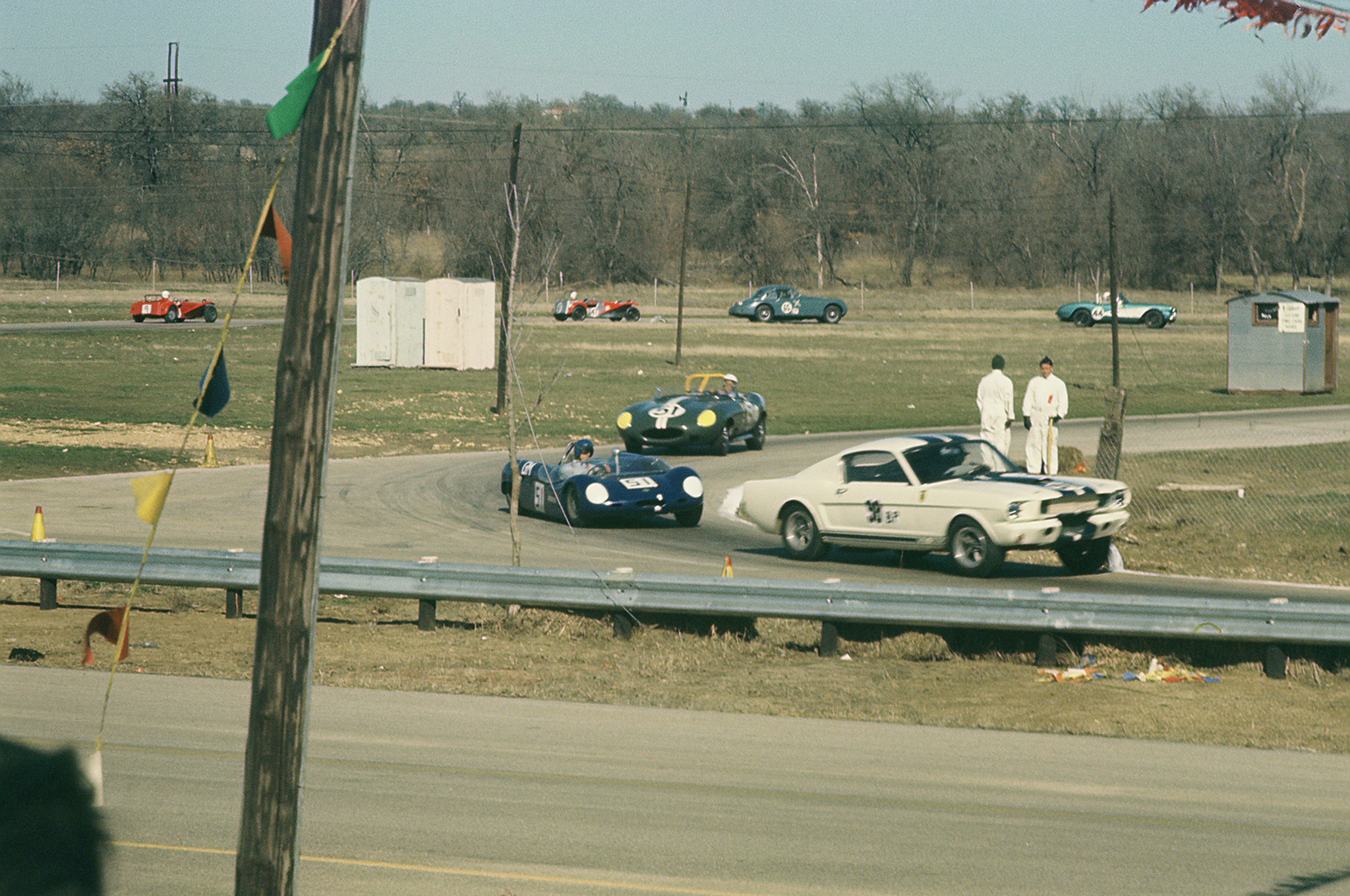 Ken Miles in the GT-350 about to enter the first long straightaway at Green Valley, in the lead of this BP-CP-DP-CM feature race that would be won by the Merlyn, #51, on Miles' tail. The Shelby, while finishing 2nd overall, would win the BP class and thus the first win for a GT-350.  The #51 in 3rd place in this photo is a BP (B Production class – same class as the GT-350) Jaguar driven by Louis Heuss, the #44 Corvette was driven by G. L. Henderson, and trialing him is another Jaguar (green), #65, driven by James Temme, followed by the red Jaguar, #41, piloted by Dave Dooley. Dave would wreck his Jaguar in this race, and later in the day would compete in Jim Thompson's '65 Mustang fastback HiPo. The last car, #9, is a red Lotus S7 driven by M. E. Grove.   (Weldon Nash photo)