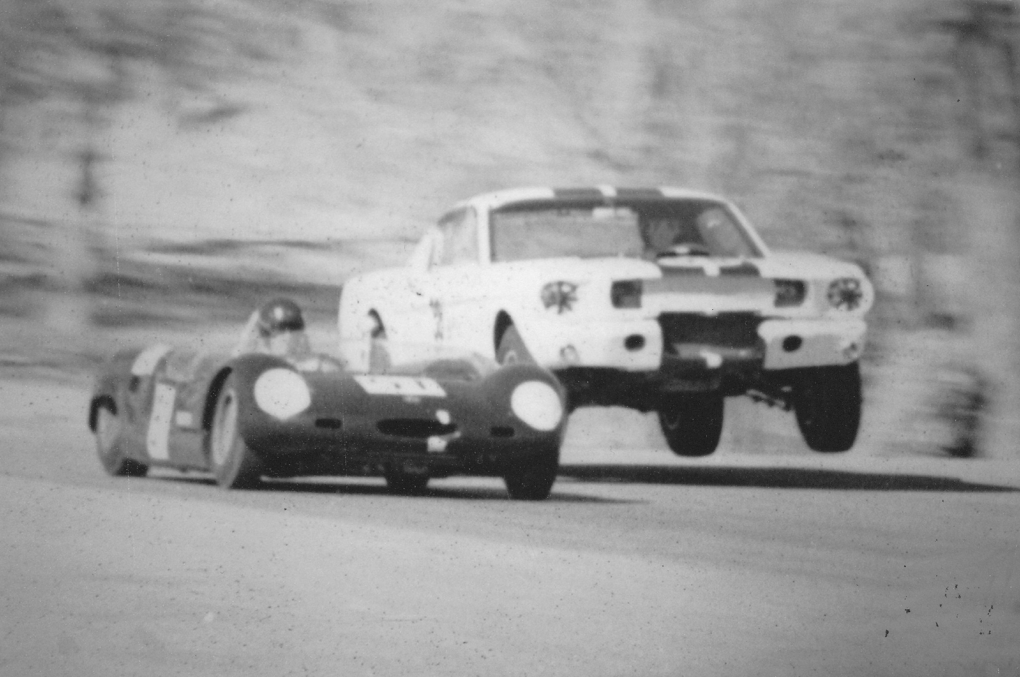 """This photo is very grainy but nonetheless famous, showing Ken Miles and his GT-350 R code going airborne while about to pass Charles Barns and his Merlyn. Alford said, """"Miles would shift into 4th gear, in the air, while leaping over the hump, with no engine whine, grinning from ear to ear. No one else was accelerating over the hump, only Miles.  The man was the fastest driver in B production that day, and was obviously utterly confident in his driving abilities. His control of the car was so smooth, effortless. His driving skills really stood out.""""   (Photographer unknown)"""