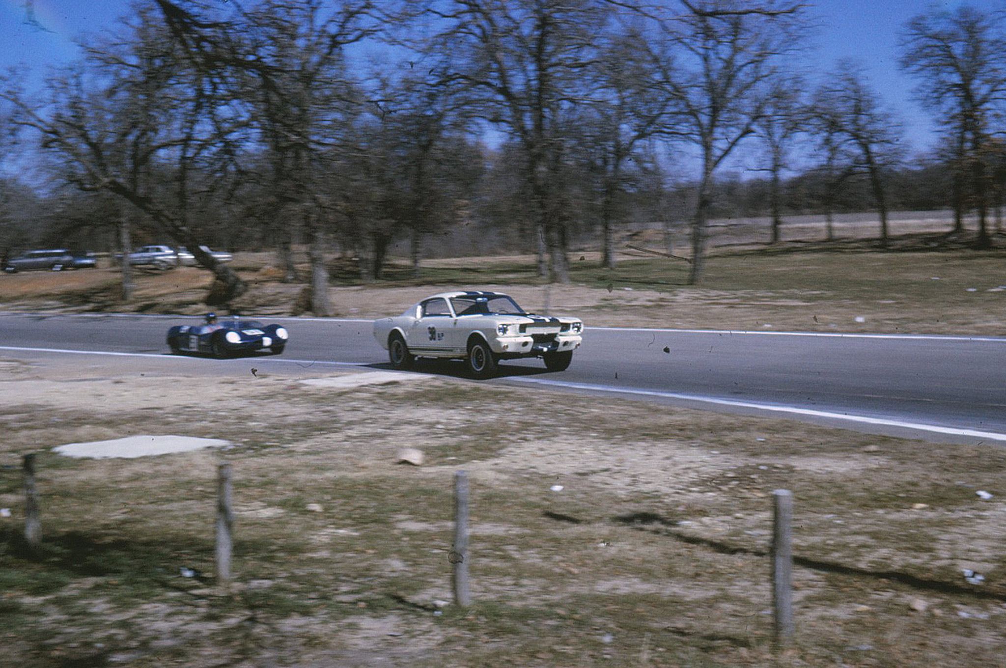 """The GT-350 R code is seen here leading the Merlyn in a preliminary race and approaching the rise in the road where the famous """"flying Mustang"""" photo was taken. Art Sahlstein pointed out that Charles Barns had tape over the drivers side grill only during the prelims, when the air temperature was much cooler than the following events. The Sahlstein's blue 1963 Fairlane 500 Sports coupe can been seen in the background, and is now in Art's possession. Several of the trees in this picture enabled Art to locate portions of the old track recently.   (Art Sahlstein photo)"""