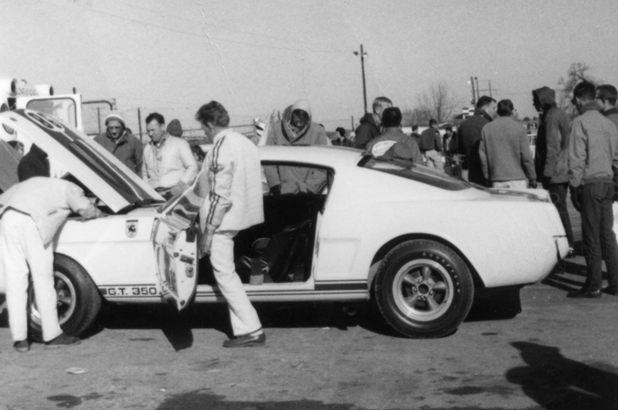 This was the first frame shot by Glenn Alford that early Sunday morning. Shelby GT 350 crew chief Ron Butler is seen depressing the gas pedal after replacing the oil filter gasket and the portion of oil lost from the failed filter gasket. On the drivers side with the long brown coat and stocking cap is Shelby driver Ken Miles.   (Glenn Alford photo)