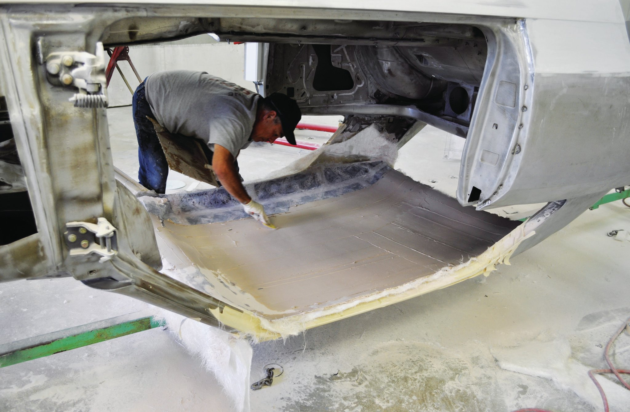The body has been installed onto a rotisserie to easily access all of the surfaces. A combination of fiberglass mat and body filler has been laid into the top to form the basis for the leather-covered headliner shell.