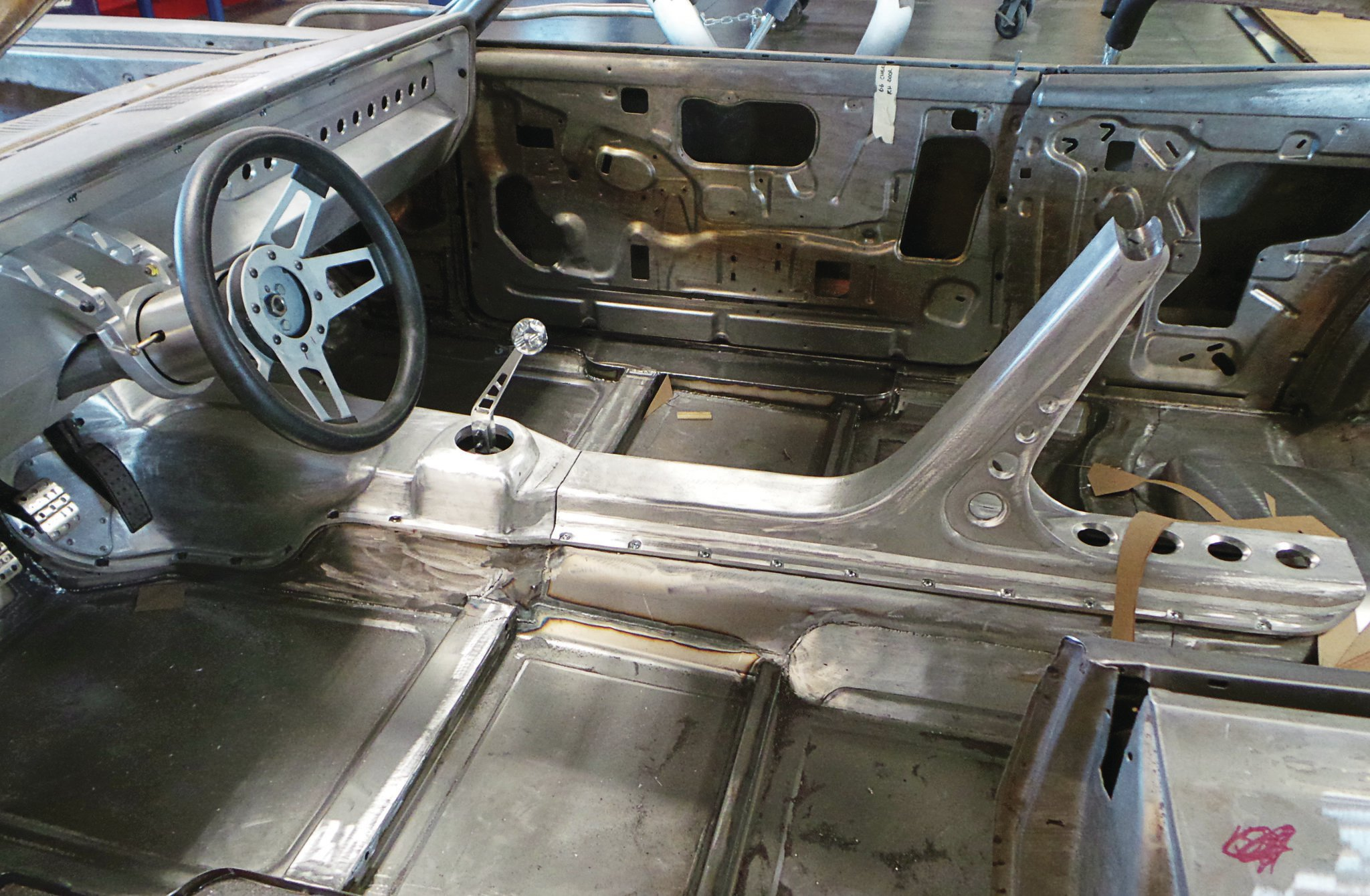 The console and harness bar support are now installed and the dash has been formed in aluminum. The elaborate steering-column support that will also hold the Racepak enclosure has been whittled in billet aluminum and trial fit.