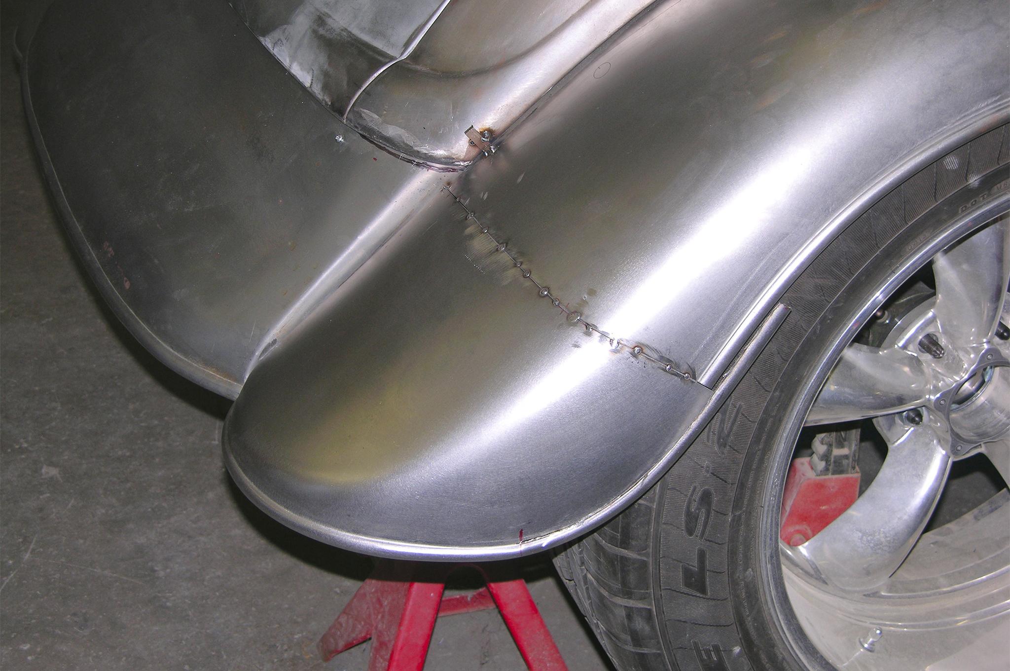 Sheetmetal modifications also take place at the rear. Here Alloway shortens the tail pan, which covers a stock gas tank and rear fenders. But they also need to align the bead roll in the fenders, as they no longer line up.