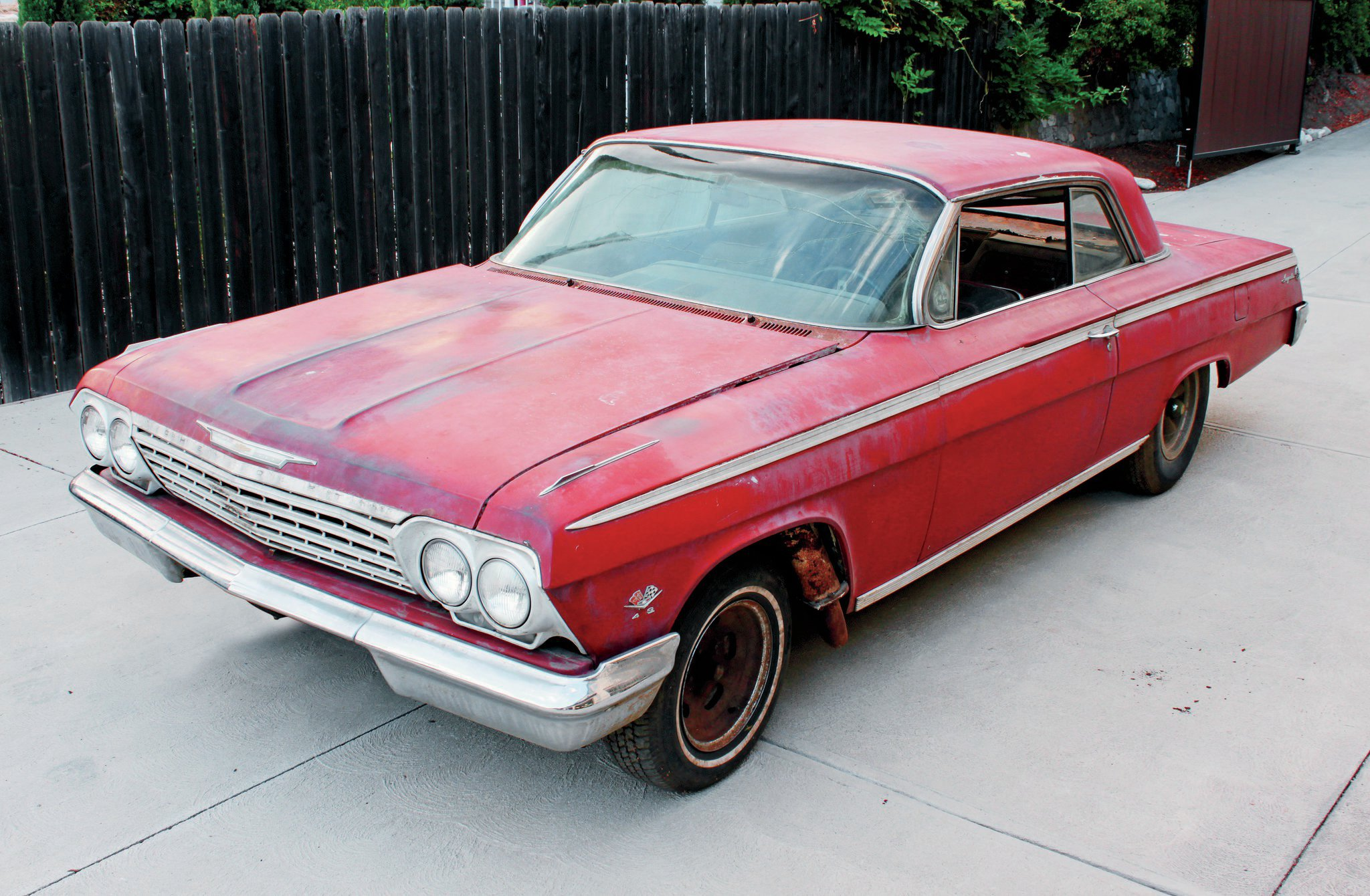 This Impala SS is a real time capsule, parked for more than 30 years still wearing it's '60s speed equipment. You can see where the original Ermine White paint is coming through the red repaint, done back in the day to disguise the winning street car.