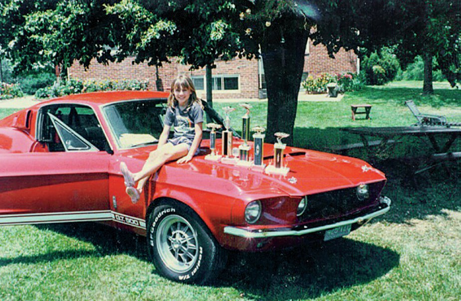 In another photo from the early '80s, George's daughter, Sheri, poses with the Shelby and some of the trophies it collected when George showed the car.