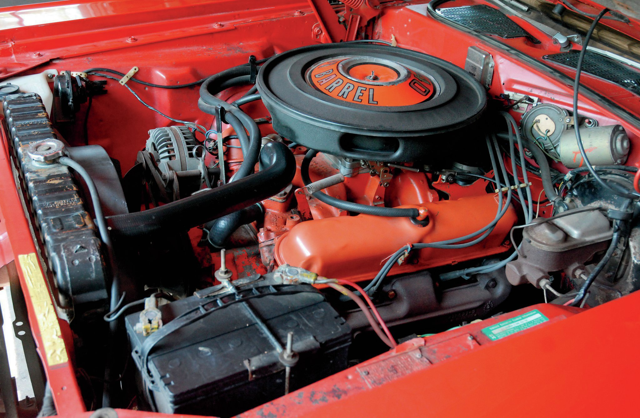 The Challenger's engine compartment still holds the original 340ci small-block. It is backed by an A833 four-speed manual rowed by a Hurst Pistol-Grip shifter.