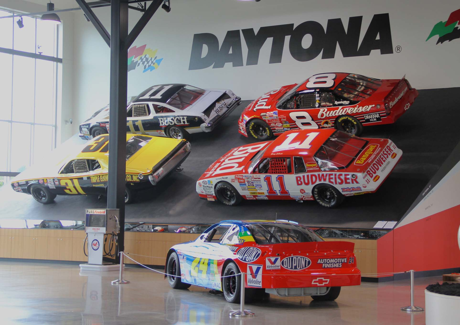 The banked oval features an accurate Daytona 31-degree bank with Terry Lebonte's 1988 Monte Carlo, Cale Yarborough's 1979 Olds 442, Jim Vandiver's 1974 Charger, and Dale Earnhardt Jr.'s 2000 Impala. These are not body shells on a wooden frame but are the actual, restored race cars. The exhibit also indicates the degree of banking for a number of other tracks on the side of the display.