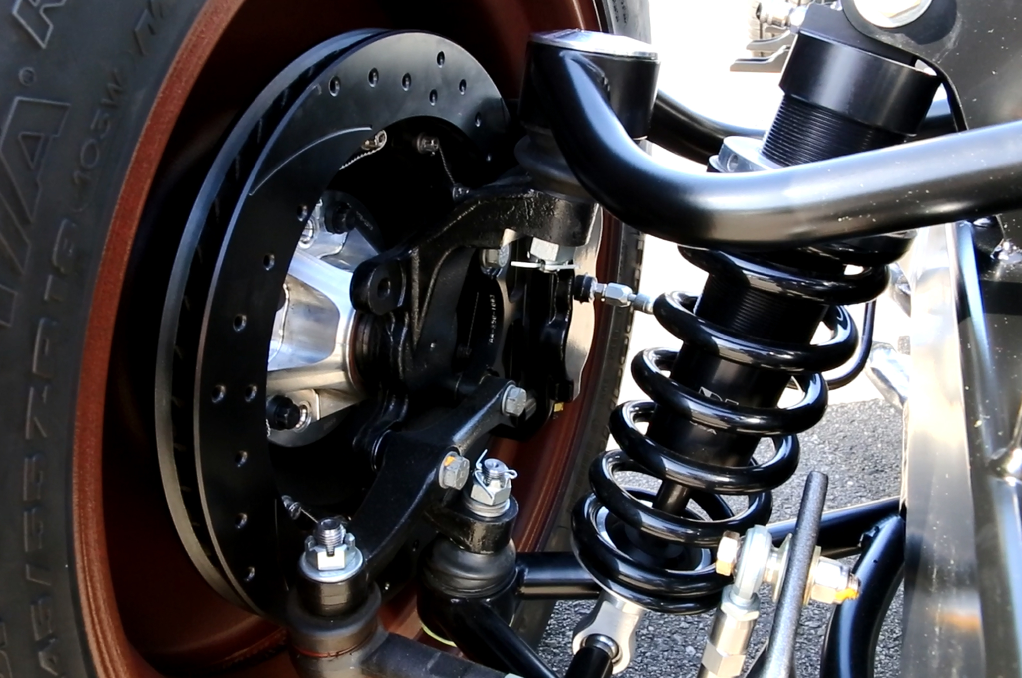 Wilwood six-piston calipers clamp a drilled and slotted 13-inch rotor in the front. A four-piston setup handles the rear.