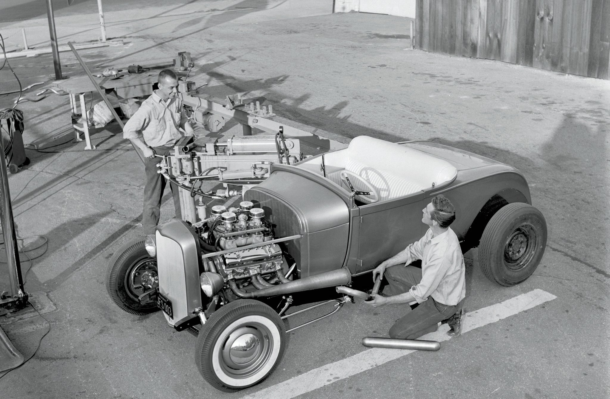 """The first time we see Sam's entire car in HRM is in the June '63 issue, when those """"Wild Outdoor Headers"""" were built. Closest to Tex's camera is Bobby Barr, owner of the muffler shop where the work was done. At the bender is co-worker Jerry Eames. At this stage, Sam and Scritch had yet to repaint the car in its final, Diplomat Blue hue."""
