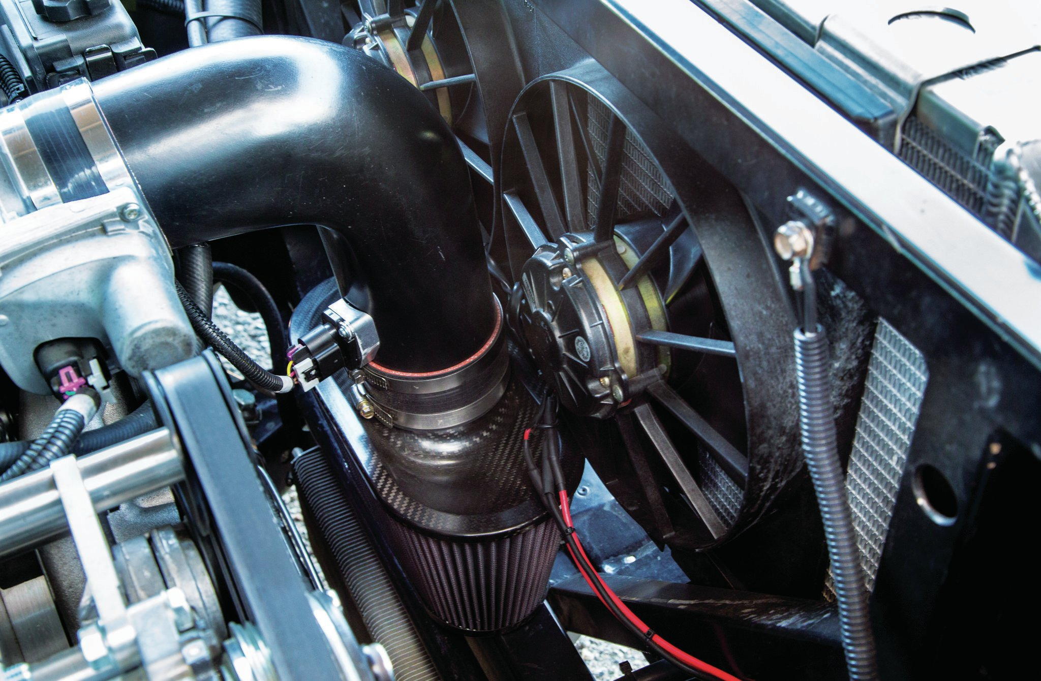 Twin electric fans help pull air through the aluminum radiator. With generous engine setback, the mass airflow sensor has plenty of packaging room. Note extra core support bracing.