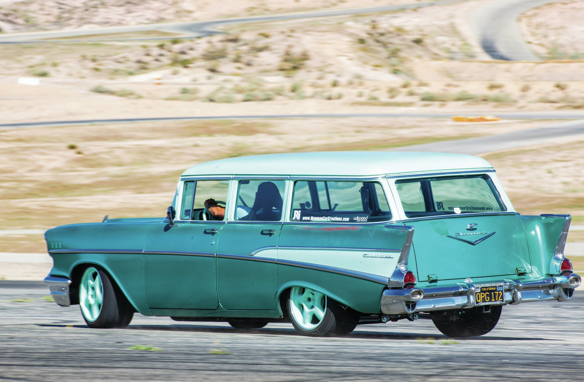 The black California plates, faded factory Highland Green paint, and wonky factory door gaps announce Kyle Newman's 1957 Chevy wagon as an original survivor, until you see the Corvette IRS peeking out under the rear bumper.