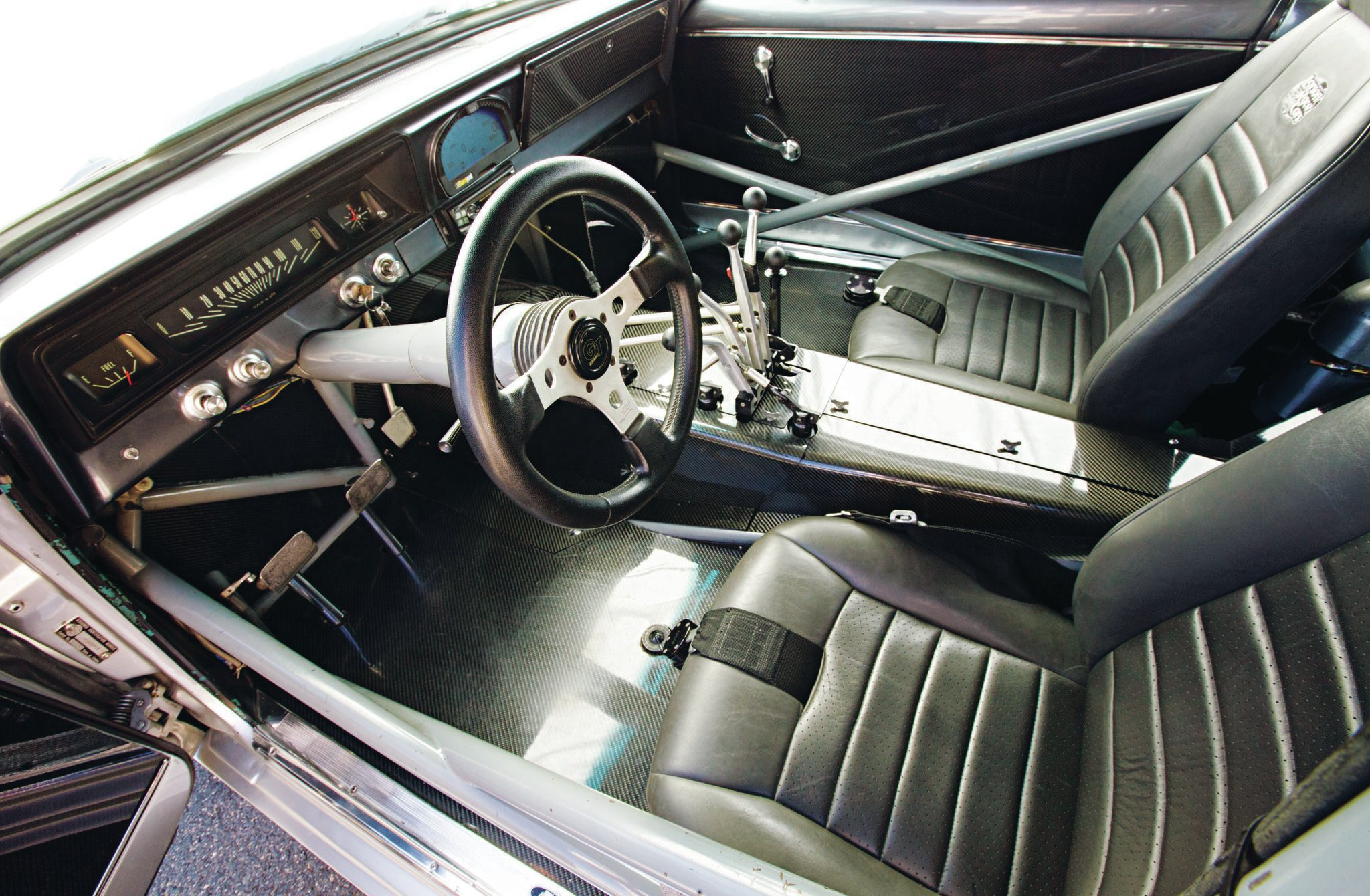 The interior always surprises people; it's not what most think a 6-second car would look like inside. The dash is original steel, and that's a tilt column with a GT Grant wheel. The carbon-fiber floors that extend from the firewall to the trunk, and the Lenco handles are the only real giveaways that we aren't looking into a Pro Street cruiser.