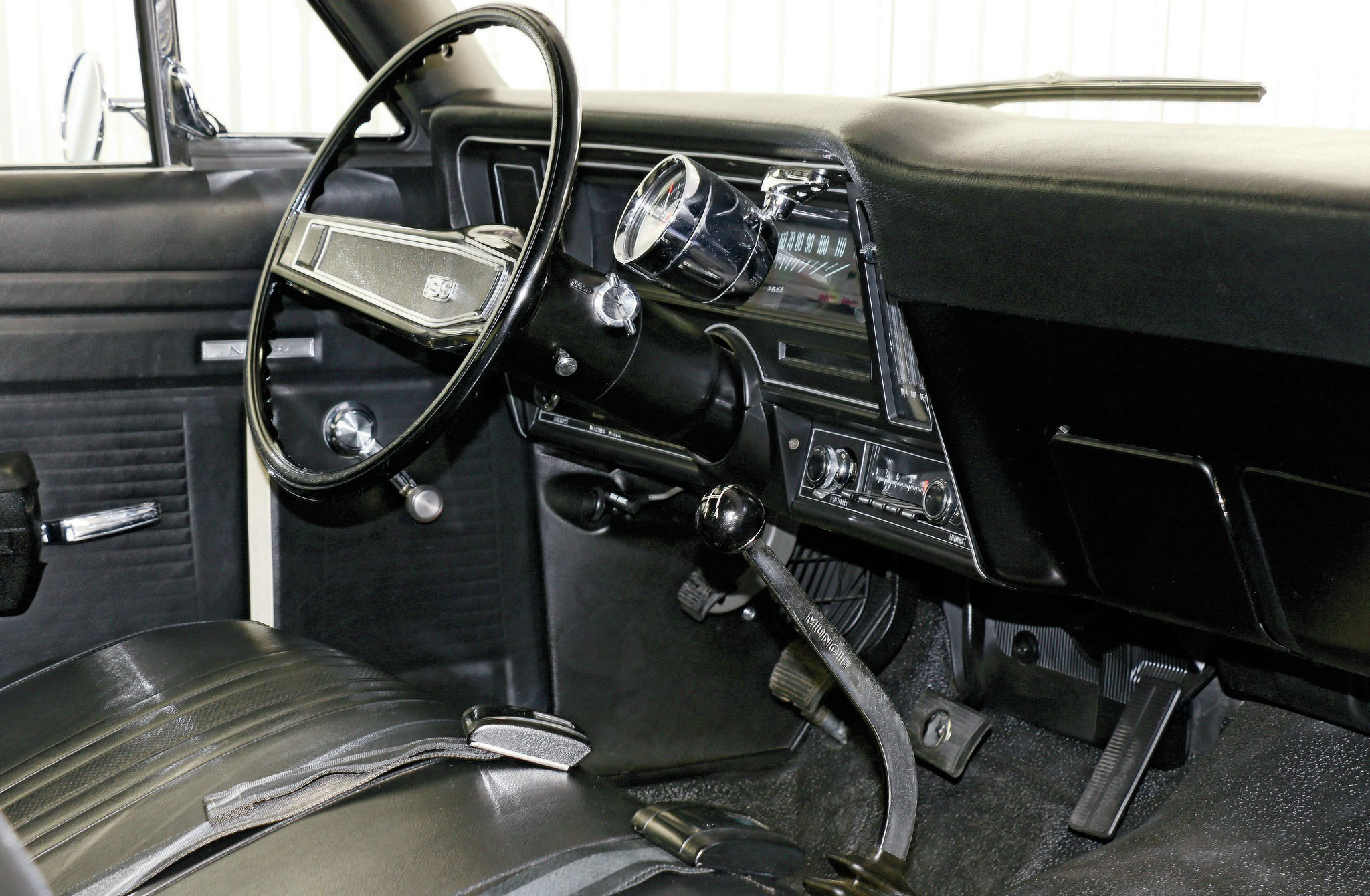Bench seat, Muncie shifter, and Stewart Warner tach amount to simple, less-is-more beauty. Muncie shifters were inferior and were often replaced with Hurst shifters.
