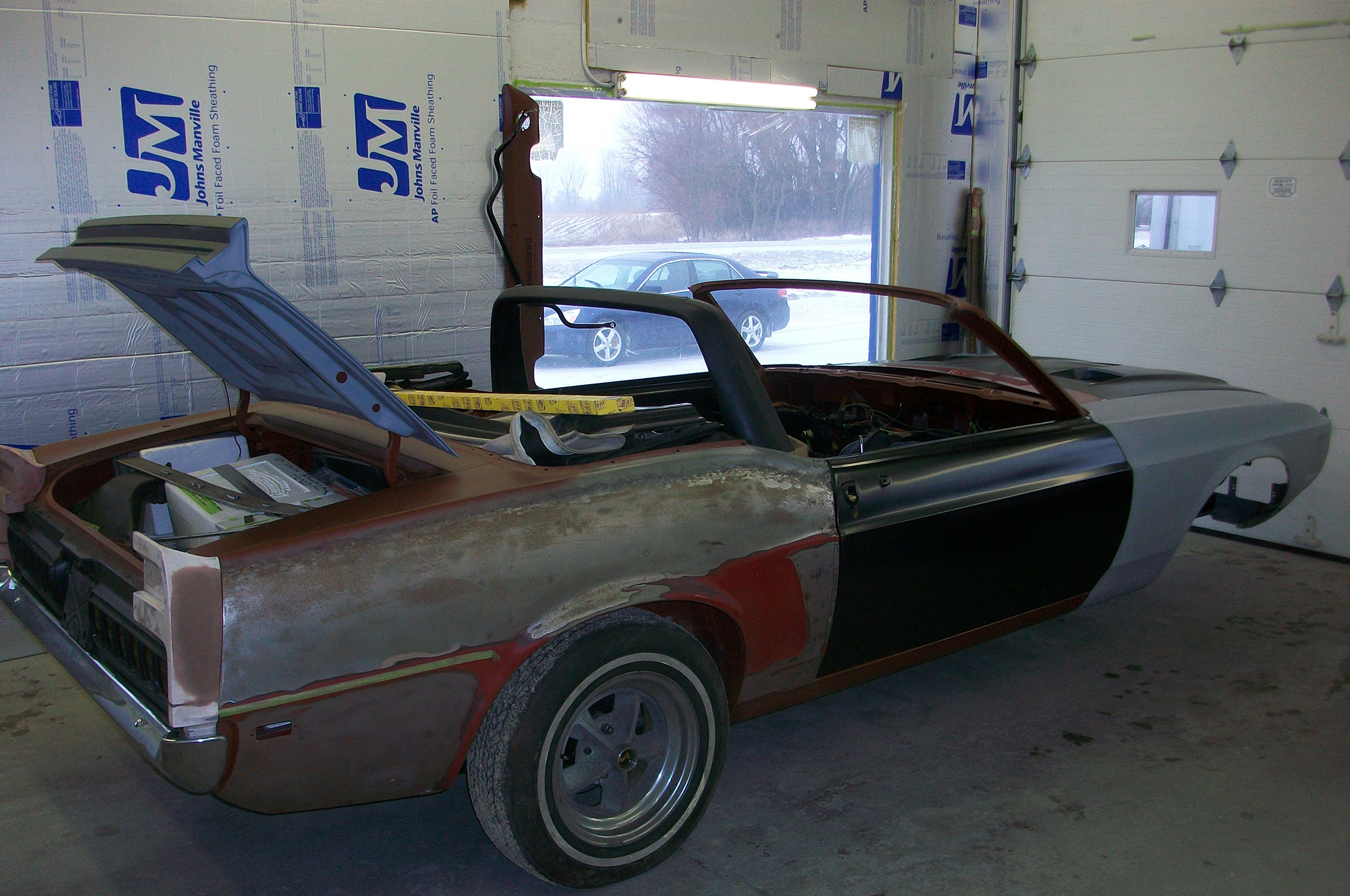 "The 1969 Shelby convertible was ready to be loaded into our enclosed car trailer from Larry's Auto Body in Milwaukee, February 2011. The car was a ""three wheeler"" in this present state, with a bolt-on center wheel to enable us to maneuver the convertible into the trailer."