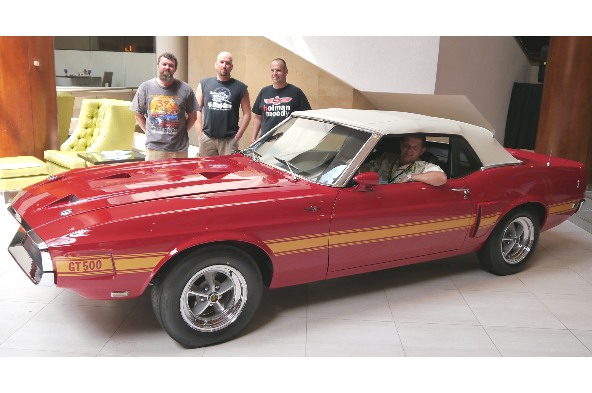"Owner Michael Smith is behind the wheel of his 1969 Gold Medal award-winning Shelby Mustang convertible, in the hotel lobby of the 39th annual Mid-America show in Tulsa, Oklahoma. ""Behind-the-scenes guys,"" from left to right, are Casey Kelly, Lonnie Baker, and Jason Billups—members of the Billups Classic Cars team."