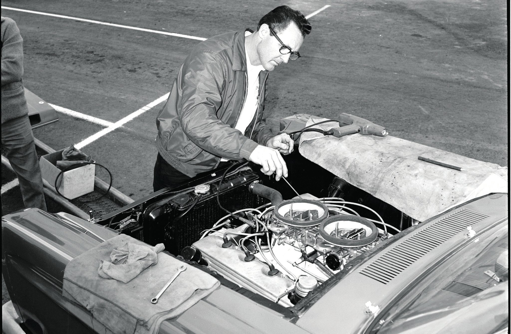 """Dyno"" Don Nicholson adjusting the carb of his Cammer in his 1965 Comet Cyclone. Dual carbs and Dyno Don tune netted 700 hp. This car would see its wheelbase altered and an 18 percent engine setback within the year to combat the altered-wheelbase Chrysler A/FX cars that were gaining on the Mercurys."