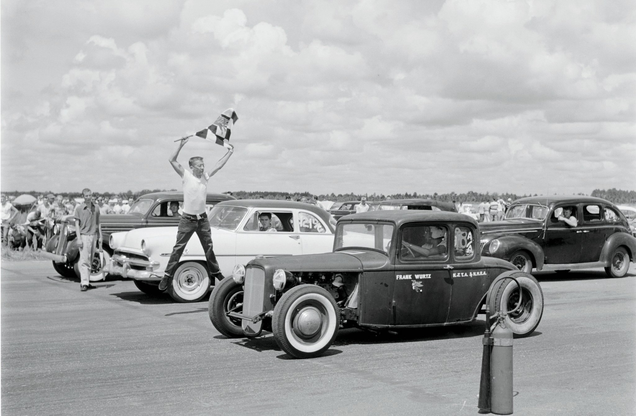 Our esteemed archivist, Thomas Voehringer, provided the research for our Flagman shot. Says Thomas: NHRA Drag Safari 1955, Lake City, Florida. The is the infancy of organized drag racing, bolstered by the NHRA's cross-country safety tour. In this shot Frank Wurtz, NHRA's New Jersey regional advisor, gets the flag for a solo run in his Merc-powered Deuce. A second flagman can be seen standing between the '53 Ford Gasser and the '35 Dodge staged in the background ('39 Ford four-door, at back right). Wurtz took First in A/Altered. He would eventually face, and succumb to, a young Don Garlits driving his flathead Merc rail job during the semifinals for Top Eliminator.