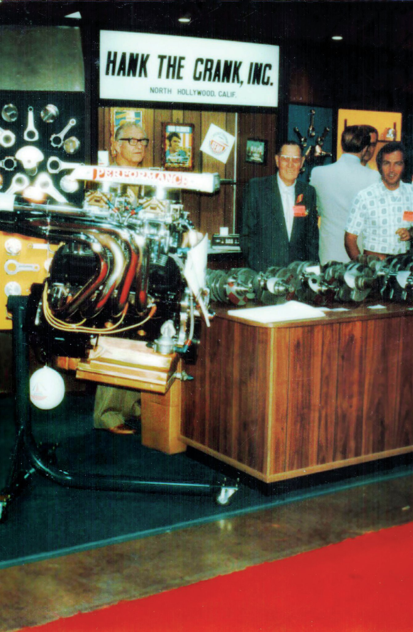 Circa 1971: The HTC booth at the SEMA Show in Anaheim, California. From left: Hank's father, Henry P. Bechtloff, HTC office manager Marcel Malinge, and Hank (with back to the camera). The big-block engine was built by Larry Parris for a marine application.