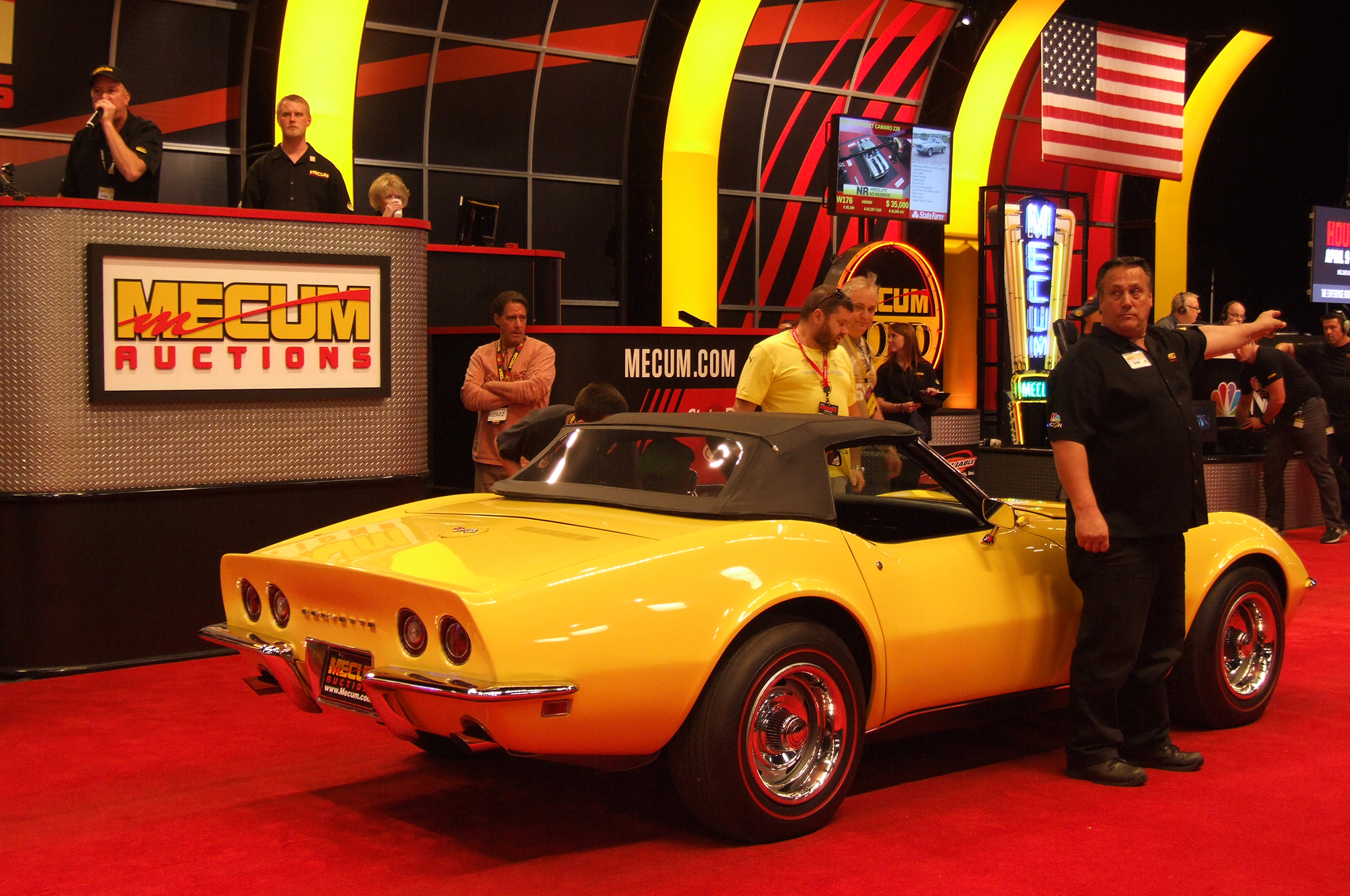 A team of Mecum bidders' assistants constantly scan the audience looking for the next bidder, while others talk to remote bidders via phone.