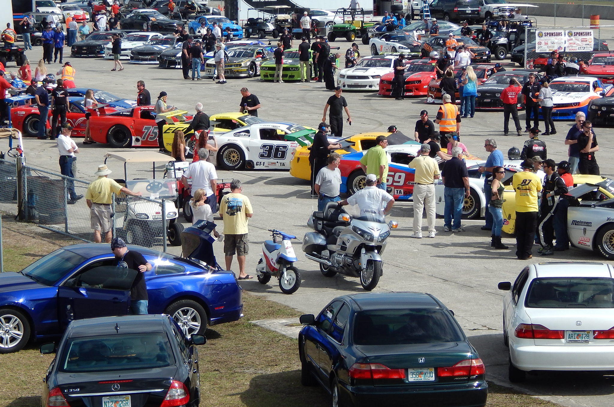 The staging area becomes very busy as the Trans-Am cars line up and drivers make final preparations.