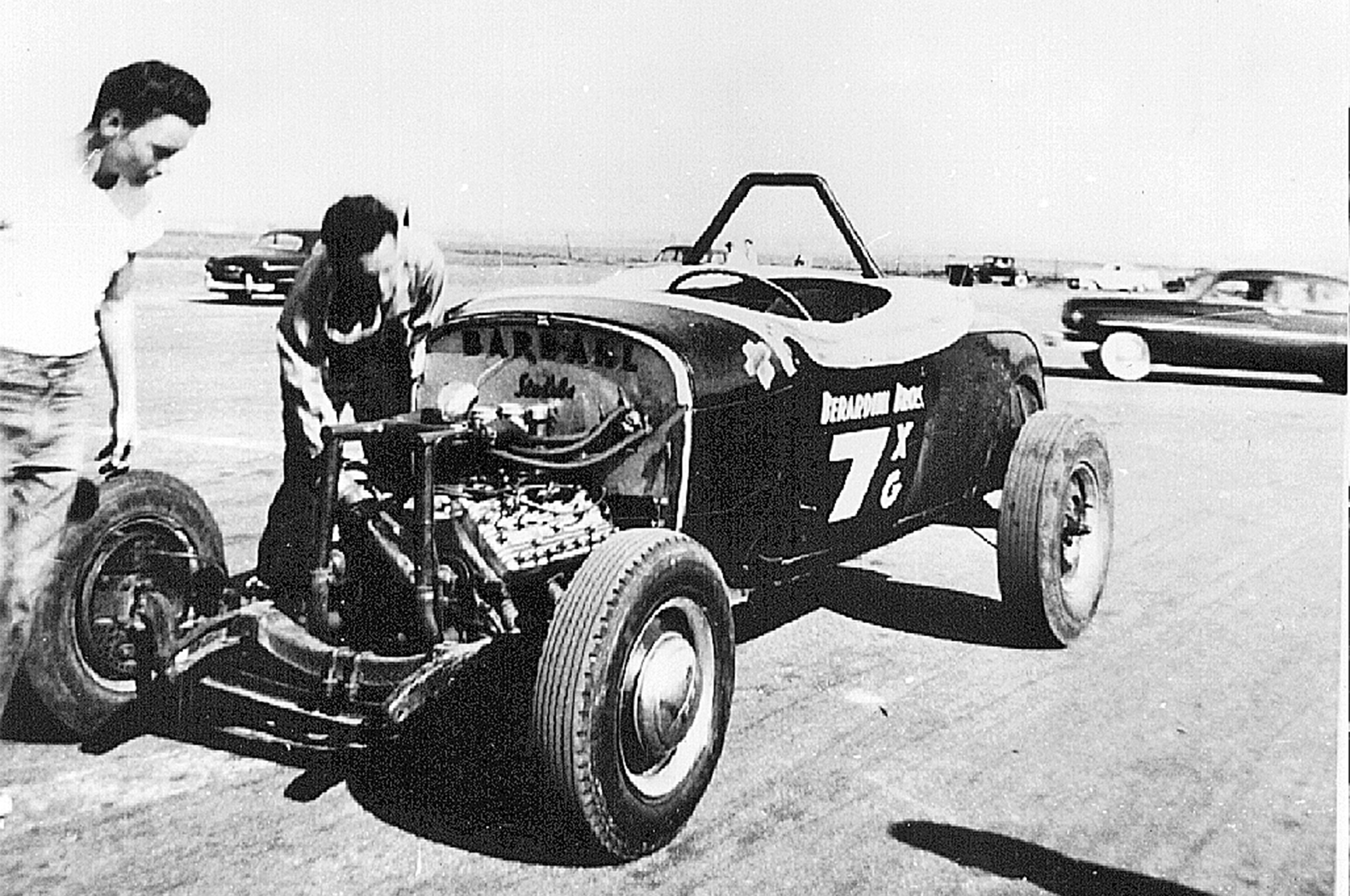 Another Leslie Long photo courtesy of the Berardini family shows Tony making some race-day adjustments to the roadster's flathead.