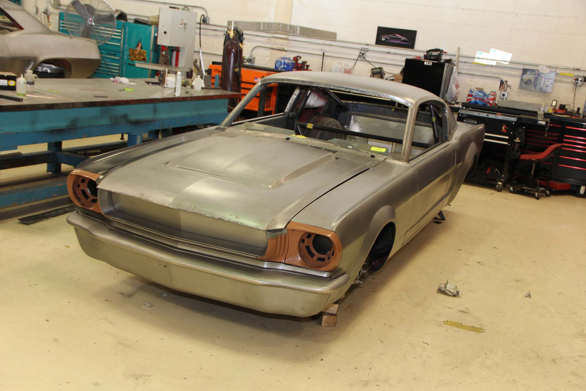 Again, lots of fabrication work on this 1966 Mustang like tasteful flairs, custom fascia, and hood. We also see a 'cage peeking out from the back.