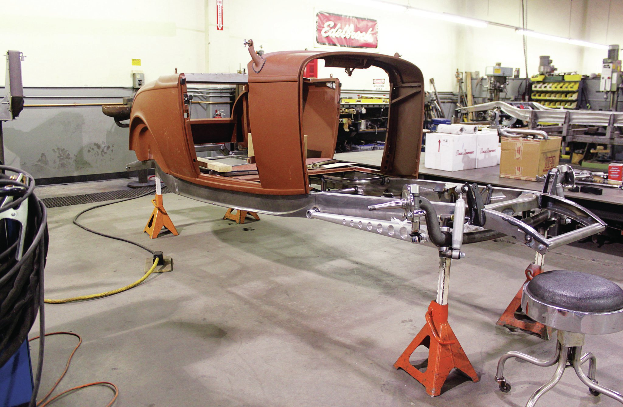 The reproduction Brookeville 1932 Ford roadster body is being test-fit to the chassis, while reinforcement has begun with a panel tacked into the body just behind the seat. One of Brizio's signature modifications is how he eliminates the two-bolt spreader bar flanges and instead locates the spreader into the front hole in the frame, then welds up the rear hole.