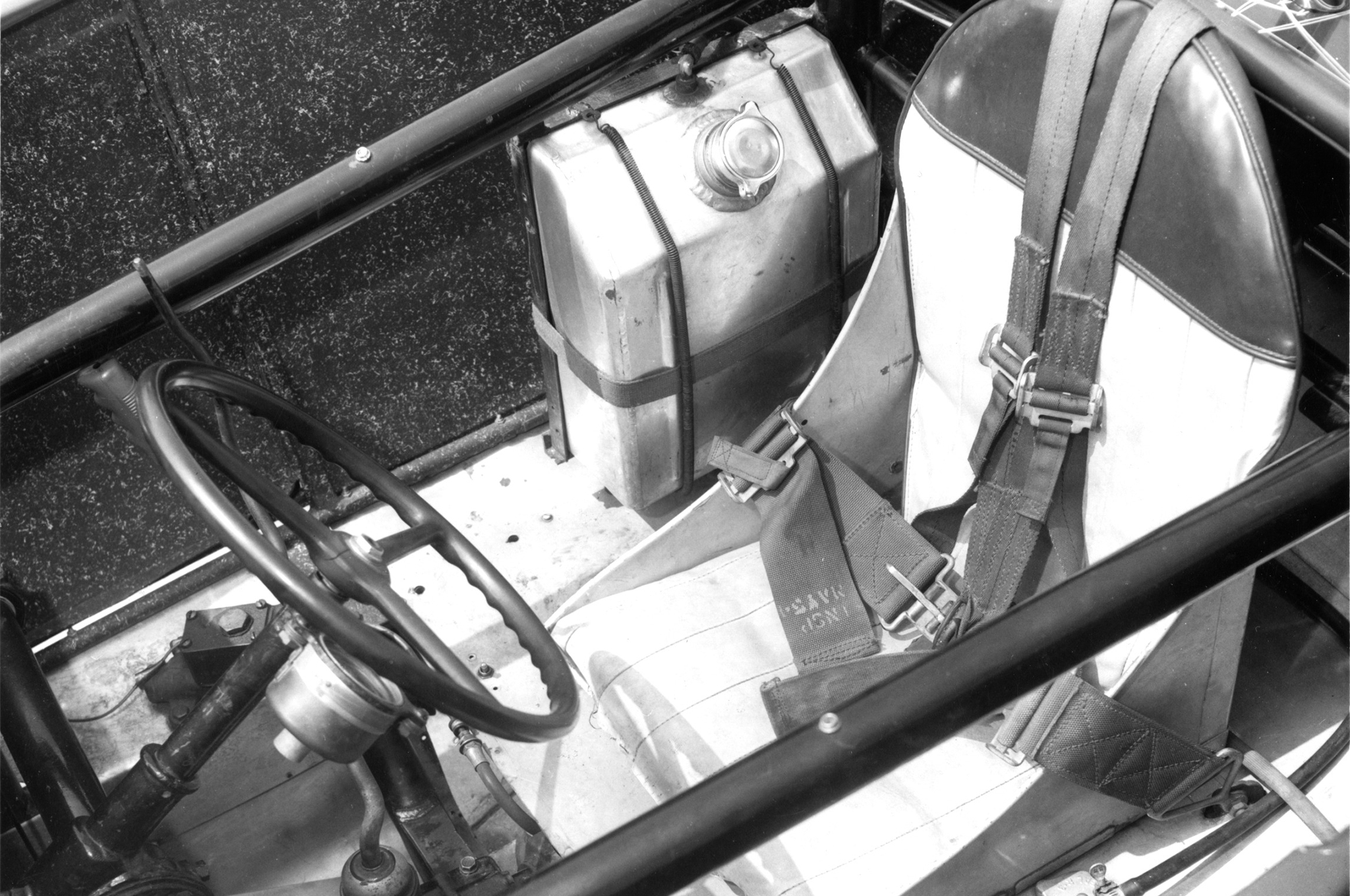 The roadster's cockpit is all business: Franklin center steering, alloy seat, side tubes and rollbar, and a petite fuel tank made from a surplus aircraft fuse box.