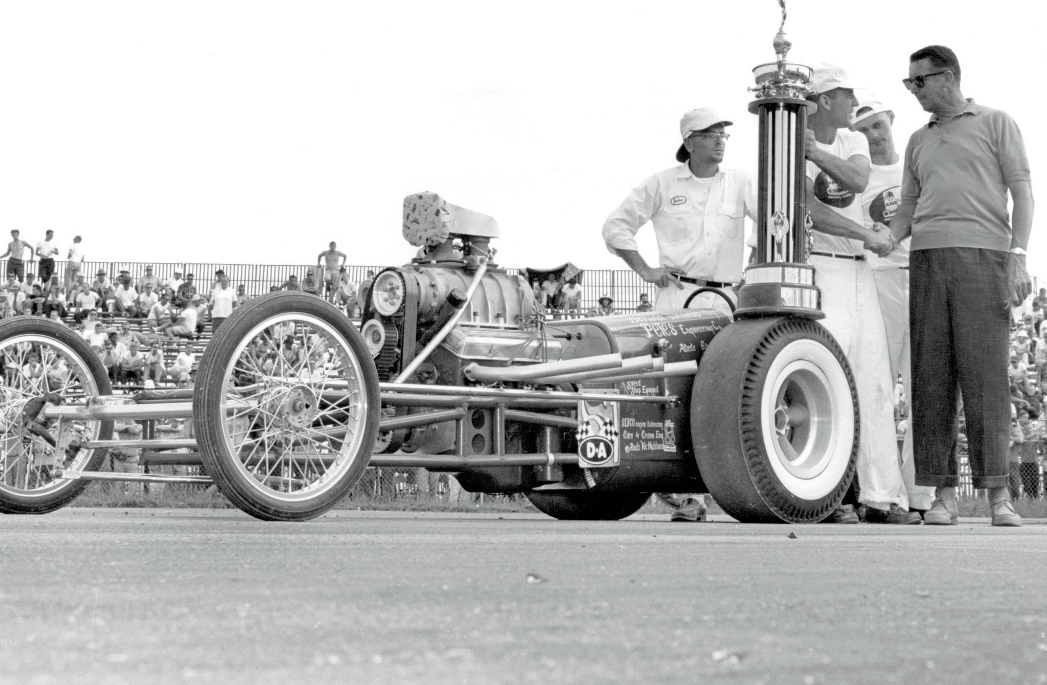 Unknown outside the South, Robinson took the 1961 NHRA Nationals Top Eliminator in the best dark horse tradition. Trophy presentation included Pete's Atlanta pal Julius Hughes (left), Pete, co-owner Bill Word, and NHRA President Wally Parks. Pete beat them all with a simple, lightweight design, sharp tuning, and heads-up driving.