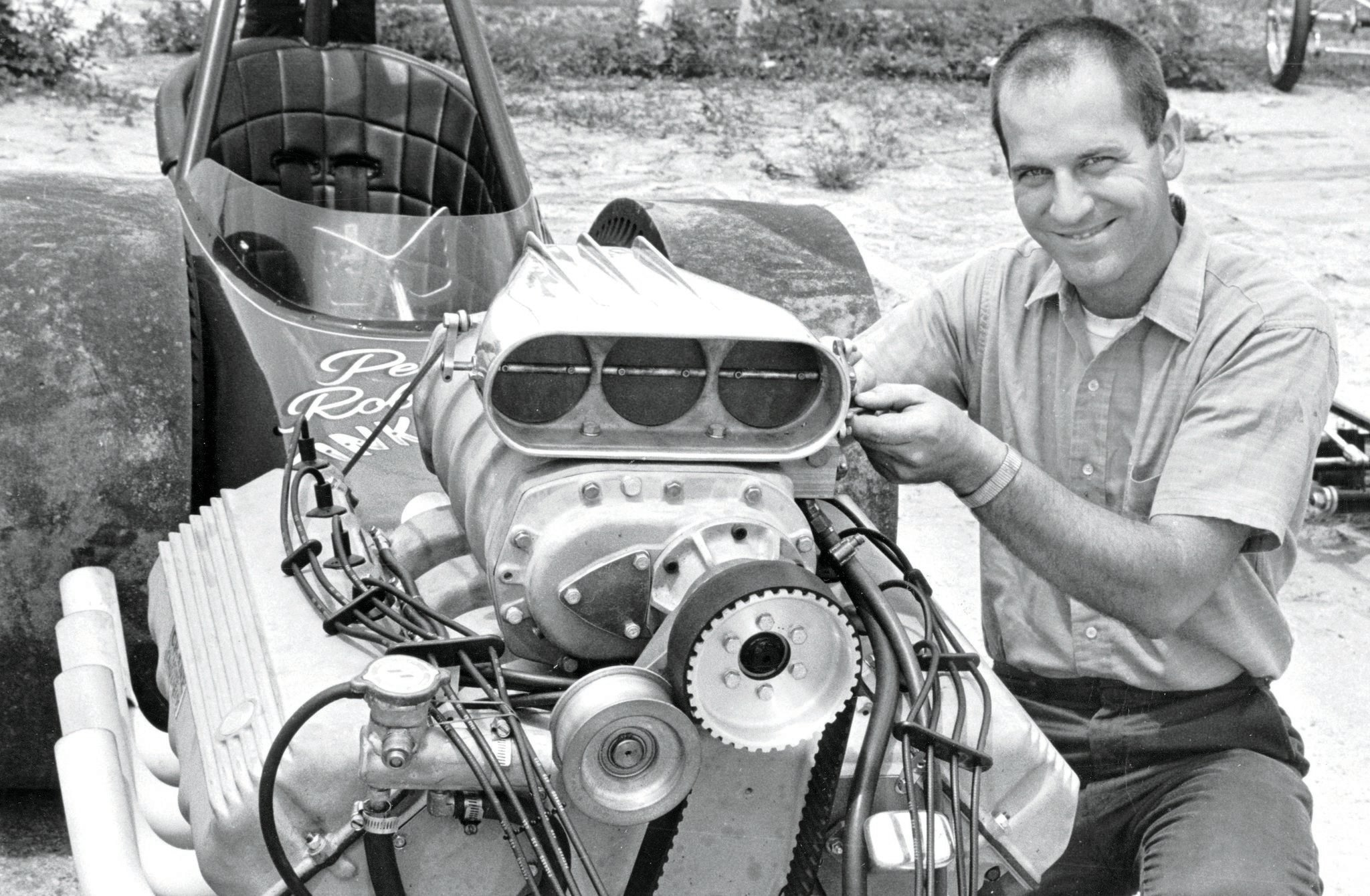 Pete is wearing his usual smile. This 1966 photo shows the 2-inch blower drive (a 3-inch version weighed a few pounds more, so he rejected it) system that he used for his early 'Cammers. He had no belt problems. But a year later, blower overdrive dictated the 3-inch setup. The cams in this engine were still chained together.