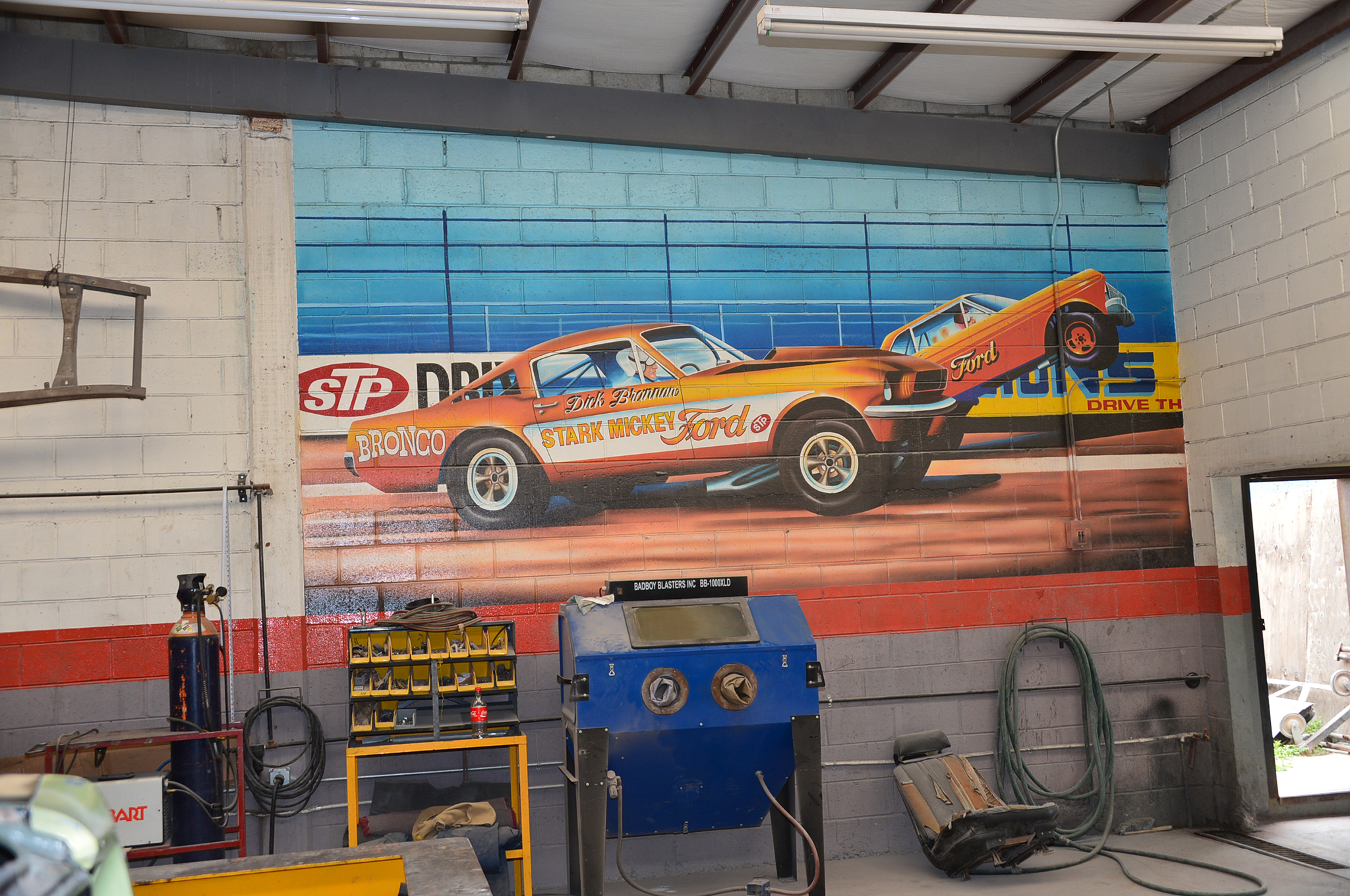 "The shop inside Street Toys shows enthusiasm for early Mustang drag cars, with this wall painting Dick Brannan's 1965 A/FX Mustang. I was amused to read ""Stark Mickey"" on the side of this 1966 Mustang—""Stark Hickey"" is the name of the Ford dealership."