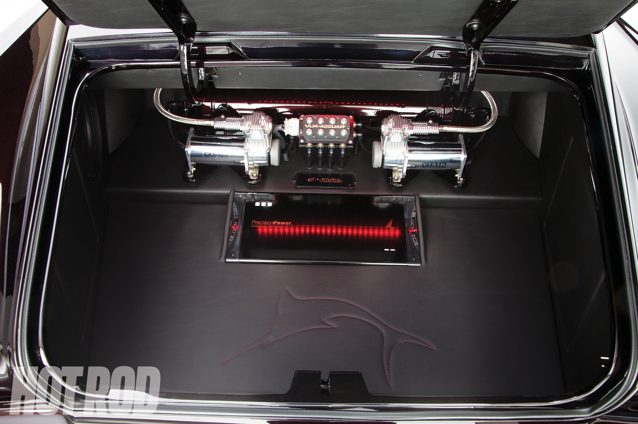 An AccuAir E-level controller and manifold are in the trunk between twin ViAir compressors. The air tank is mounted just ahead under the package tray.