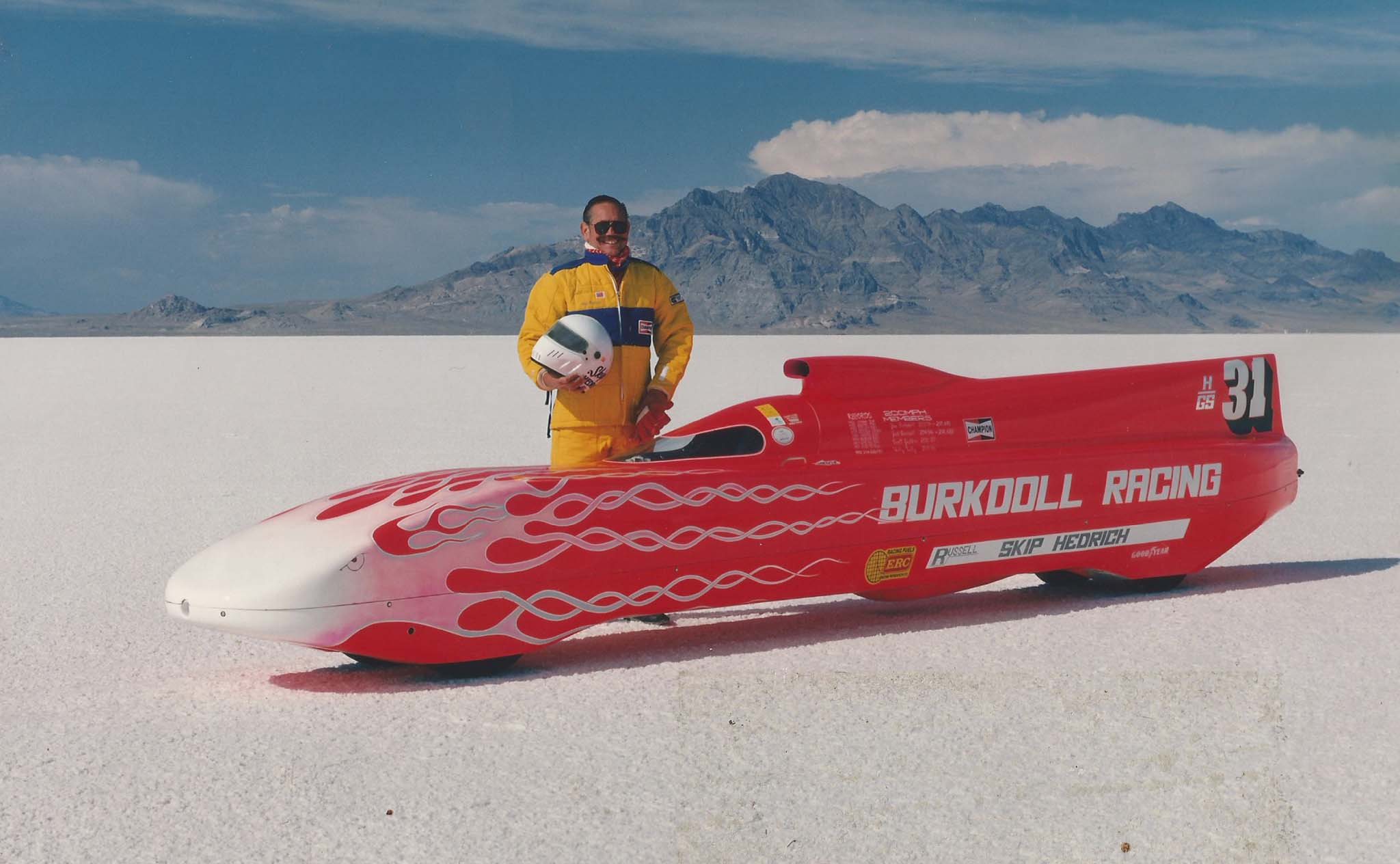 """When Skip returned to Bonneville in 1990, he met Jim and Juley Burkdoll and struck up a conversation about their streamliner. """"I told Jim about my background, Jim put me in the car, and by 4:30 that afternoon I had my SCTA license."""" Before Skip moved on to build his own land speed racer, he reached close to record speed in class of 214.426 mph. """"I drove for Jim and Juley for two years before I decided to build my own car in `96. We had a wonderful relationship."""""""
