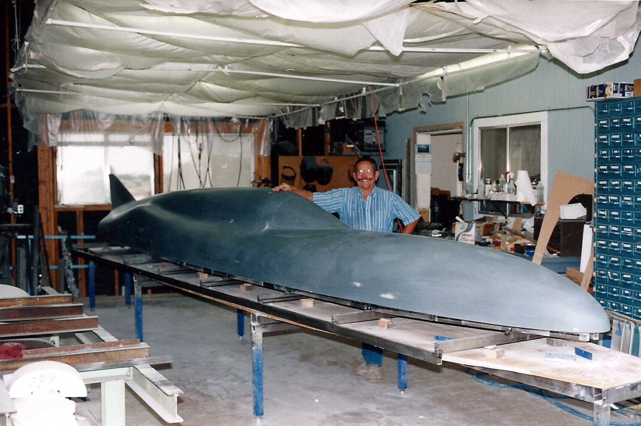 """The construction of Skip's streamliner was a complicated affair taking five years to build. """"I envisioned a streamliner that was most importantly aerodynamically sound,"""" says Skip. He worked with aerodynamicist Lynn Yakel, whose experience included work with NASA, to create a body """"like an airplane fuselage, excluding the wings."""" Here, Skip is standing behind the top half of the plug used to make the fiberglass streamliner body."""