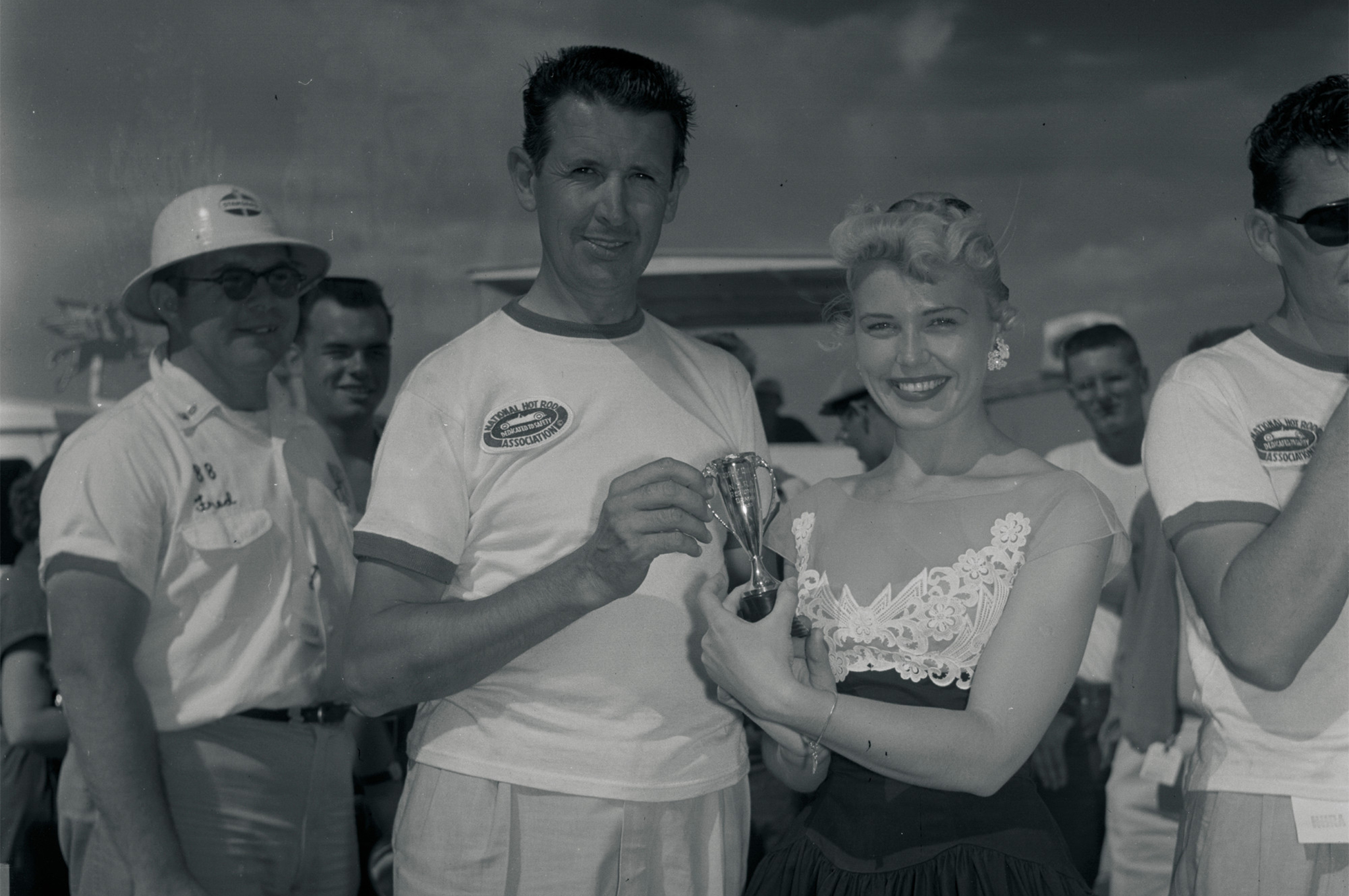 "Wally Parks was uncharacteristically frisky in Denver's winners' circle. As the presenter of a trophy inscribed ""Trophy Queen, NHRA Regional Drags, 1955,"" he enthusiastically reversed roles with recipient Mary Saunders and issued the congratulatory kiss. After his body-crushing lip lock, the NHRA president, HOT ROD editor, and Petersen editorial director returned to form—except for what appears to be a lipstick moustache."