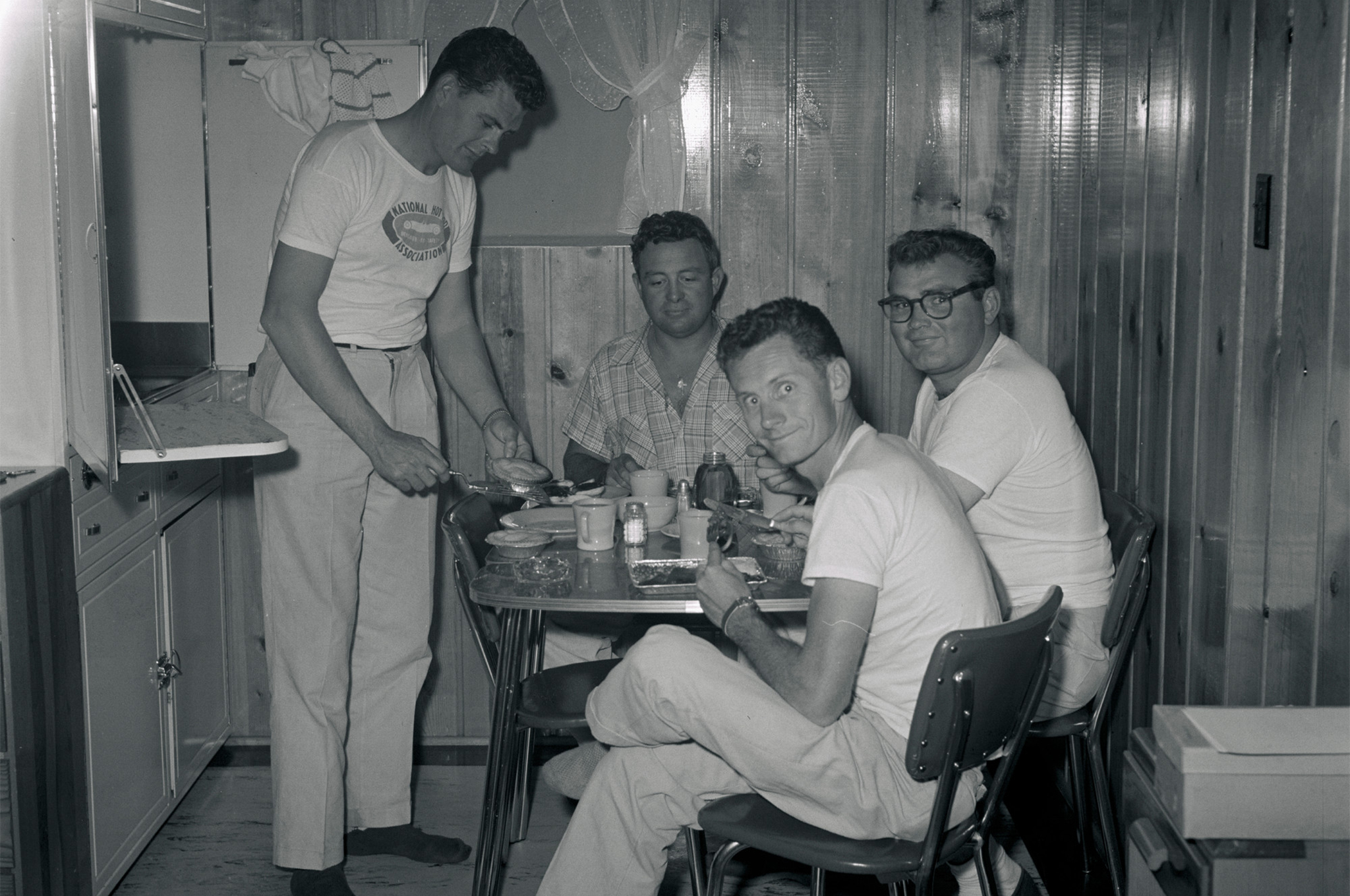 "Eric Rickman often remarked that because he worked for HOT ROD, which made money, instead of NHRA, which did not, ""I could have steak every night, while the other guys ate hamburger."" Tonight, though, it looks like TV dinners all around for (left to right) Bud Coons, Rick, Chic Cannon, and Bud Evans. Cannon, the sole survivor, is writing a book about his experiences."