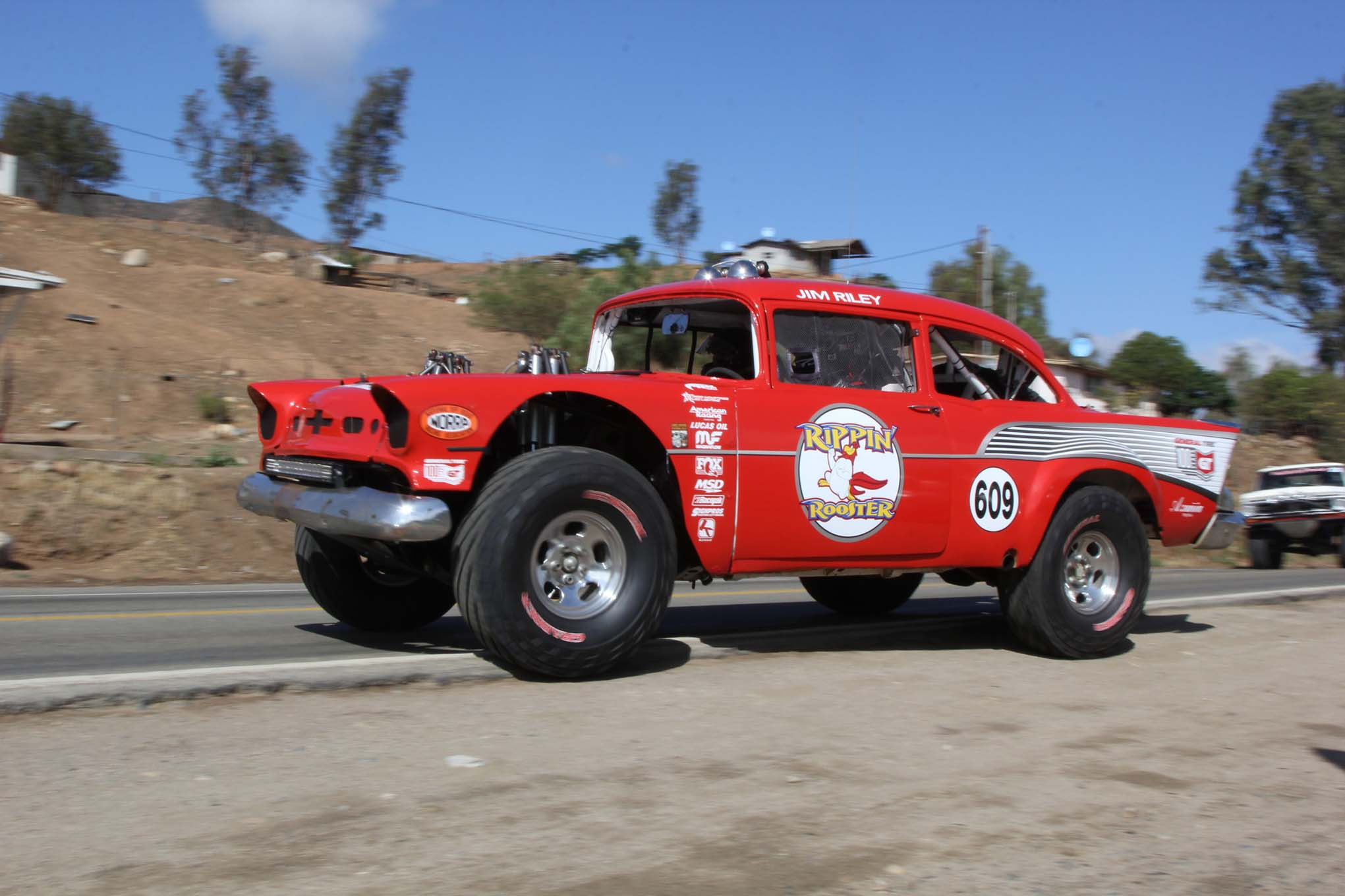 The Rippin' Rooster 1957 Chevy was originally a 1955, but off-road racing tends to go through body panels. The car was built by Larry Schwacofer in the 1980s and won multiple class championships, five in the Baja 1000. Today it races in vintage classes, with Jim Riley at the wheel.