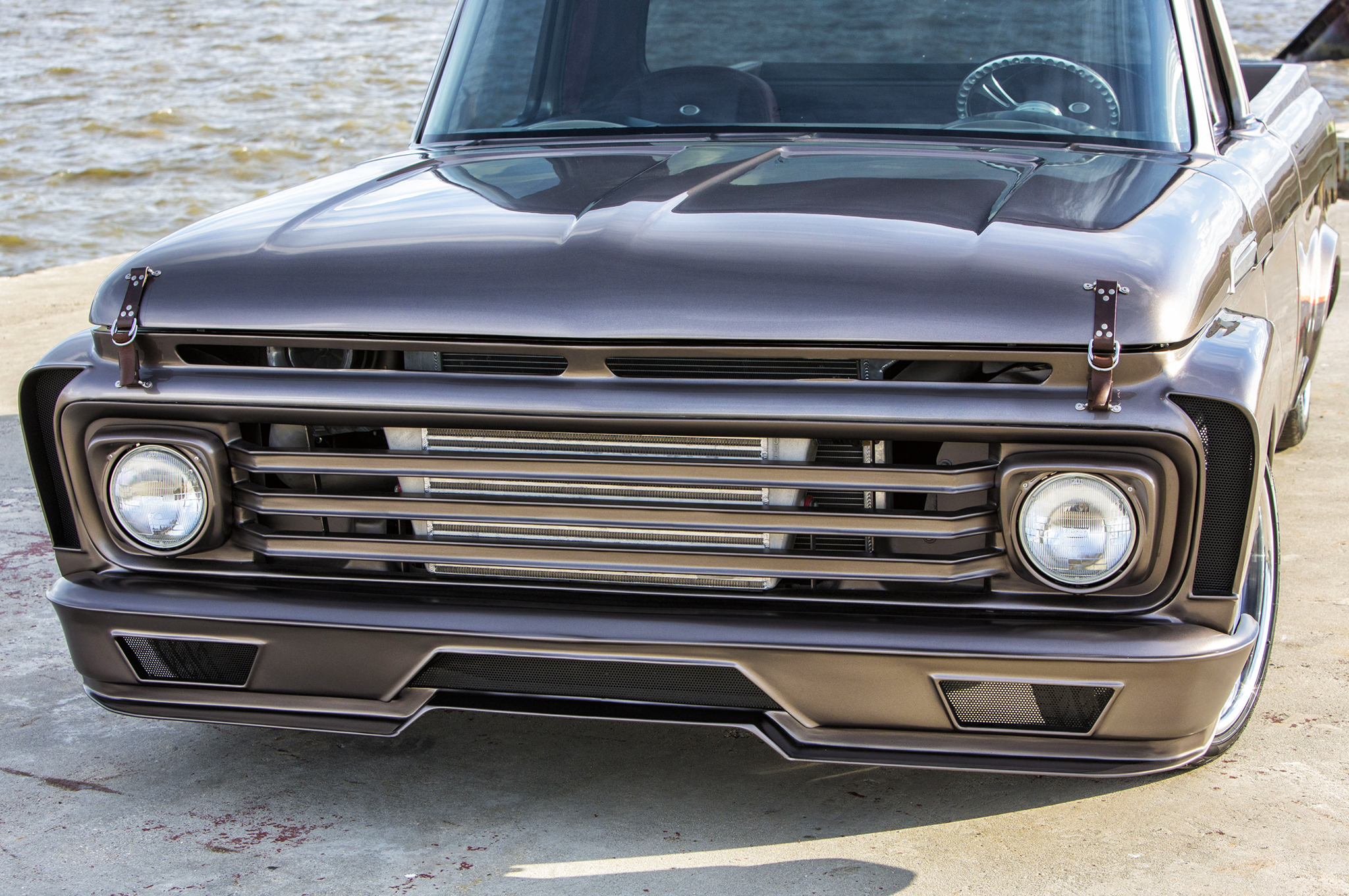 The custom triple-bar grille is reminiscent of a late-model F-150 and the custom bumper uses trapezoidal openings that match the rear.