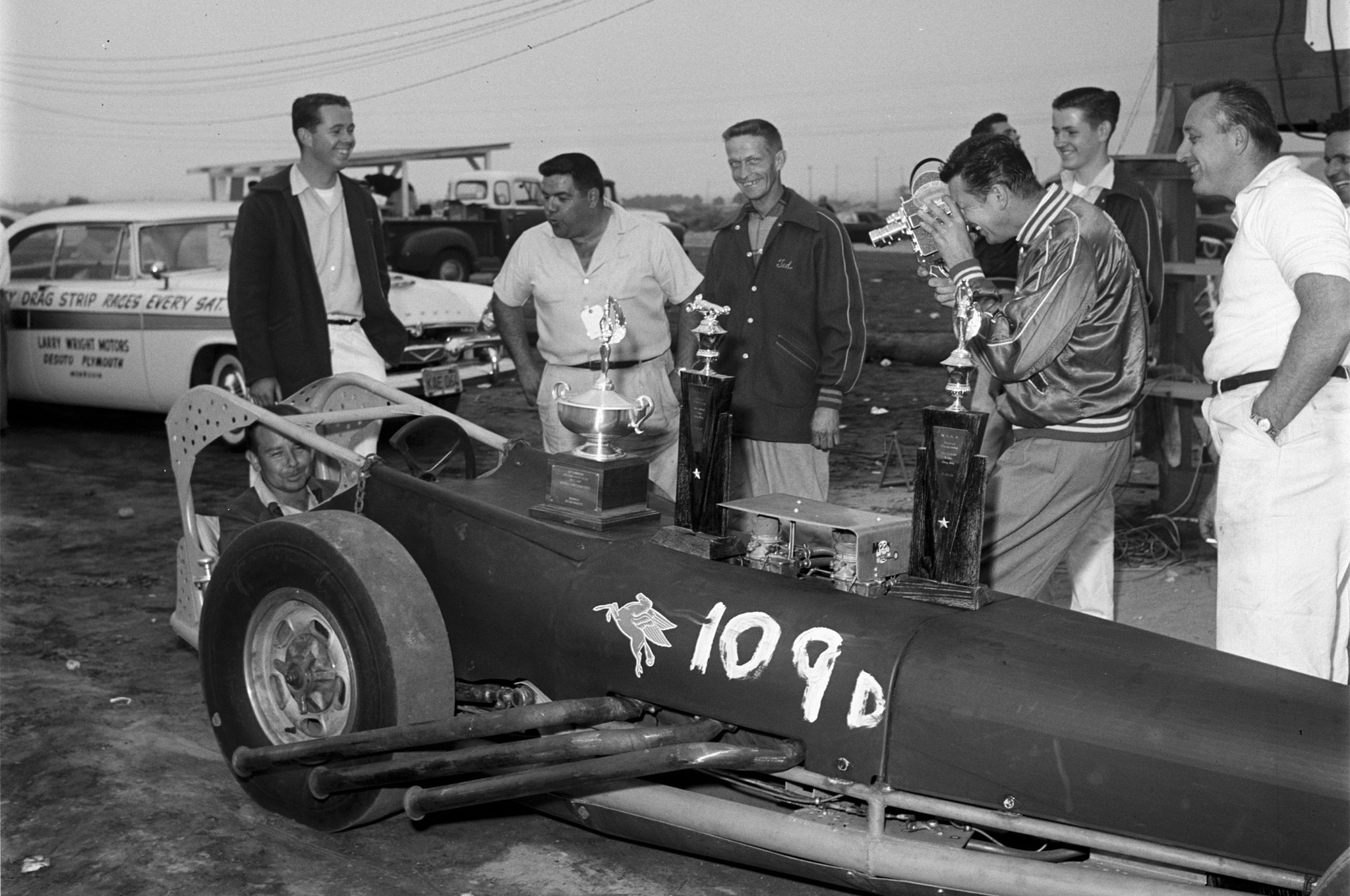 """Nothing here suggests the acrimony to come between Scotty Fenn (far right) and the Yeakel Cadillac Specialists team led by Lou Baney (third from left), nor the media war later waged by Fenn and Wally Parks (with movie camera). Baney, Kenny Arnold (seated), and their crew are celebrating a big Top Eliminator win at San Gabriel's West Coast Regional Championship Drags (Aug. '56 HRM) with a rail that Scotty built for himself before leaving Oklahoma. Considered the prototype for Chassis Research Co.'s popular TE-440 model—short for """"Top Eliminator, 440 Yards""""—this Cad-powered slingshot evolved into the Cook & Bedwell car."""