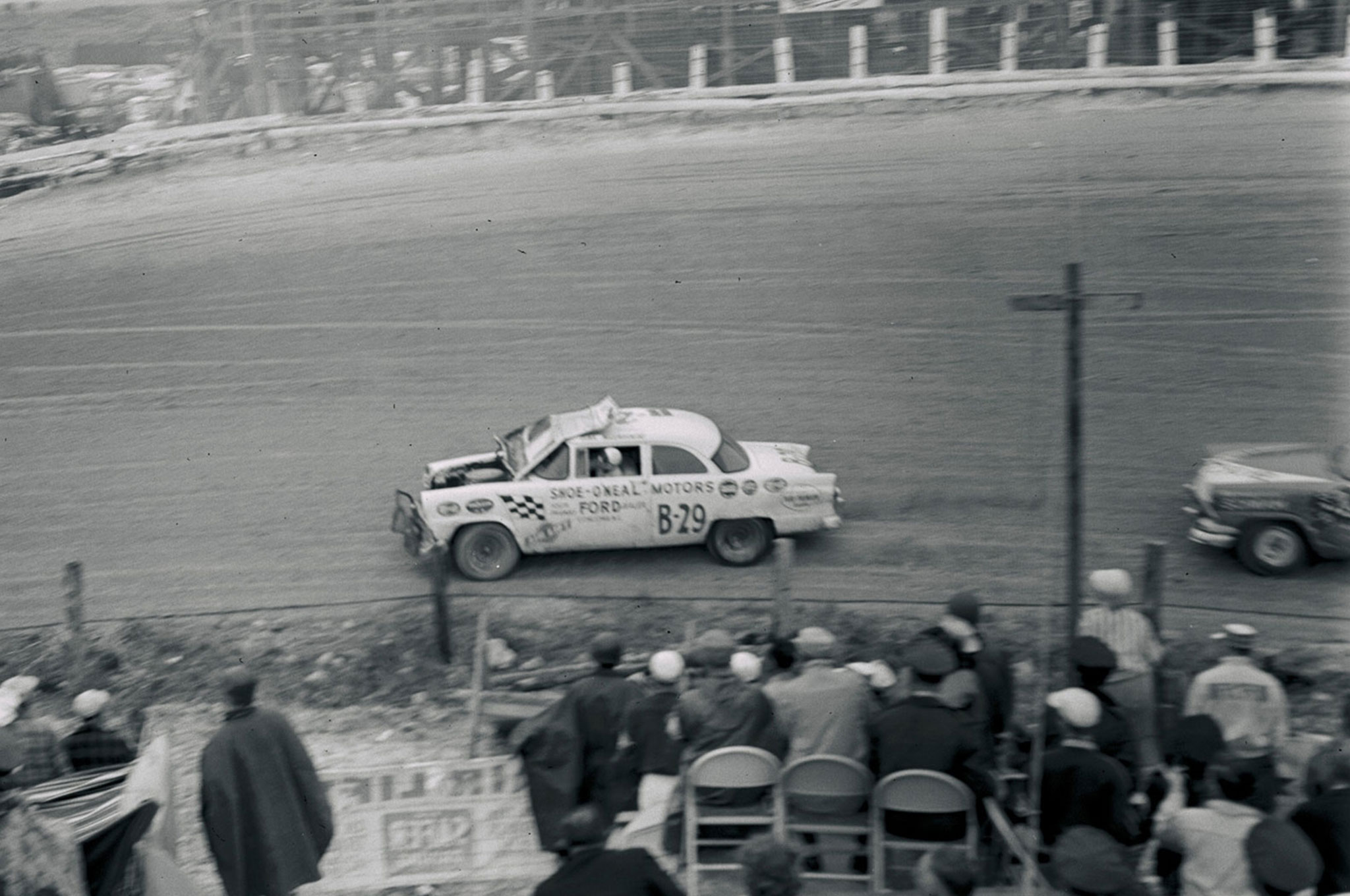 Dink Widenhouse's 34th-place Grand National finish was somewhat miraculous after two spinouts and whatever contact caused this temporary obstruction. Wally Parks got the shot, and another from the same spot after the Ford had shed its hood.