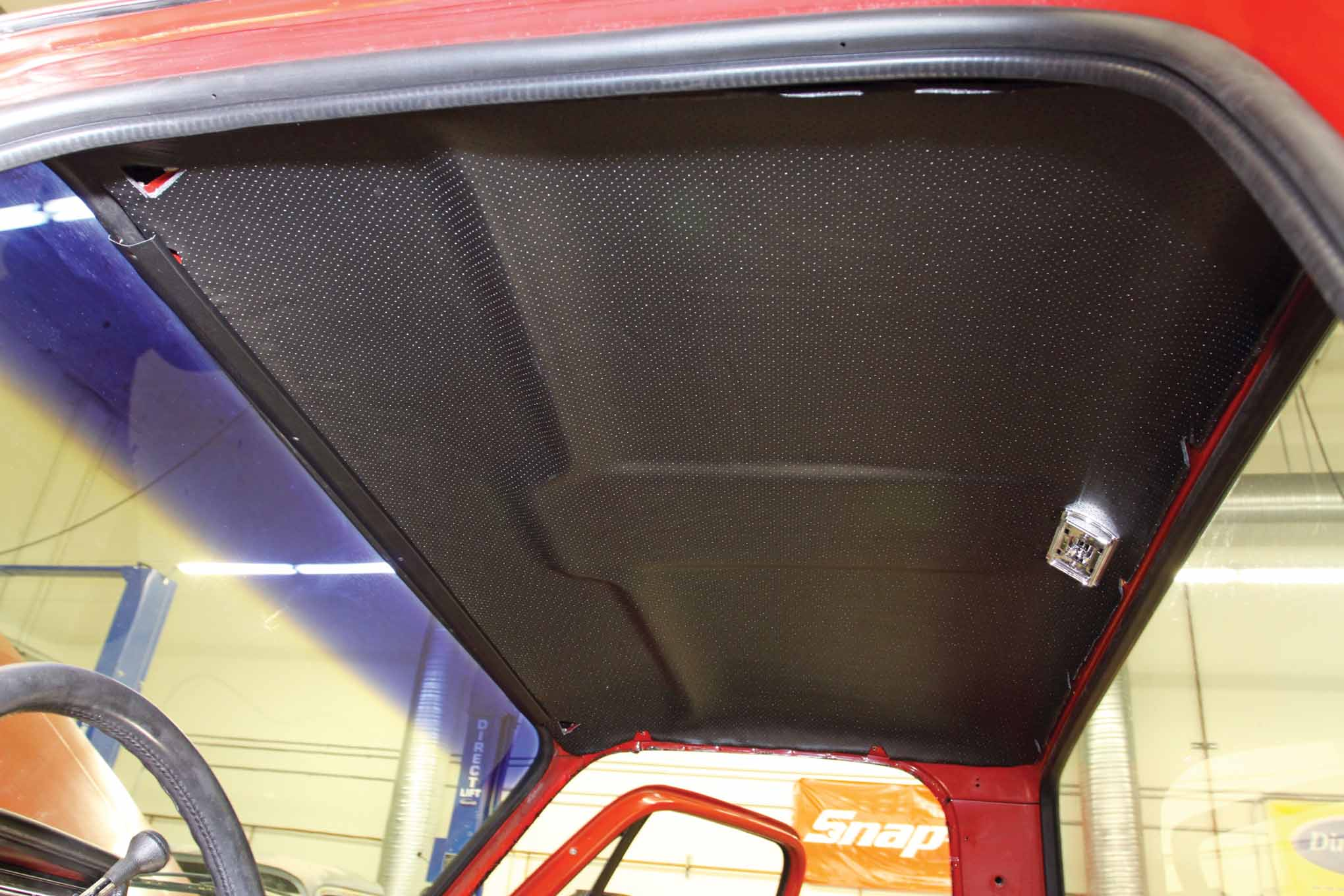 With the help of a second person, the front and rear center interior cab moldings were installed to hold the new headliner in place.