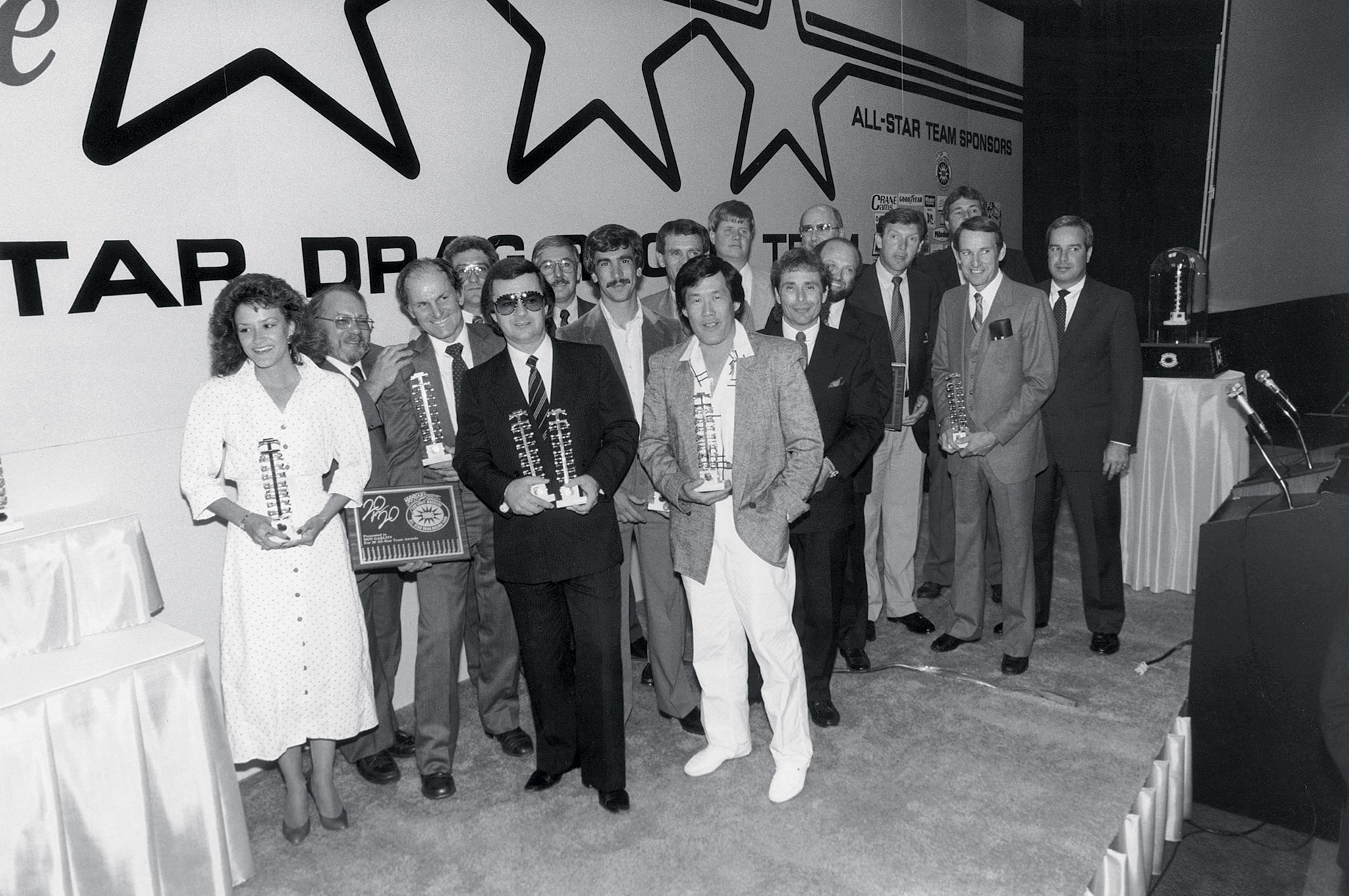 "In 1986, Roland Leong (right) was awarded the Ollie with Joe Hrudka (in glasses) accepting two sponsorship awards for his Mr Gasket company. Other winners that year were Bill Jenkins (a special ""20 for 20"" acknowledgement), Don Garlits, Bill Maropolus, Bob Glidden, Tim Eckstrand, David Reher, Buddy Morrison, Kenny Bernstein, Jerry Haas, Dale Armstrong, and several others."