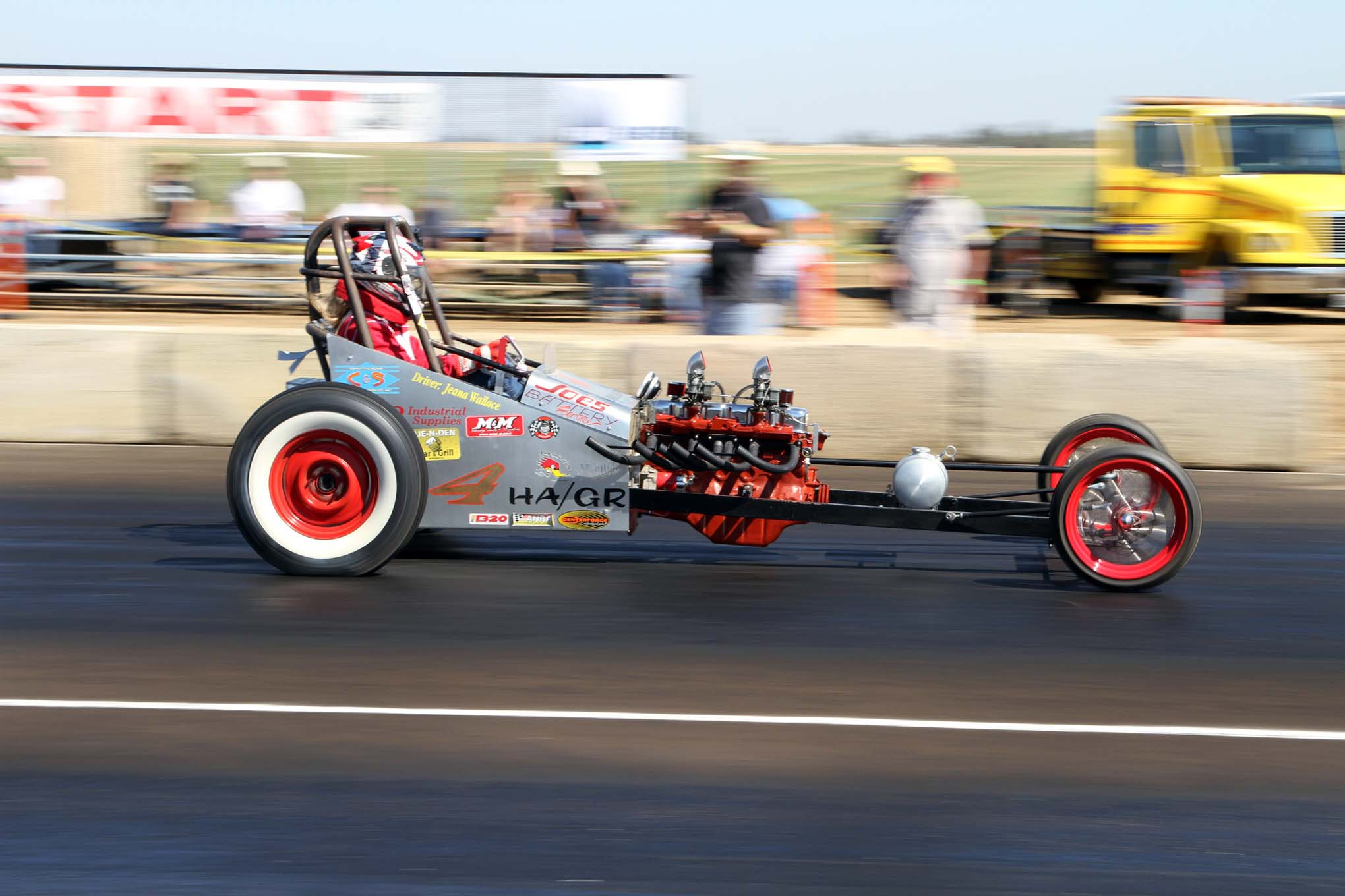Jeana Haskins was wed just one week prior to the races at Eagle Field. She held off her honeymoon with her husband to go racing with her HAMB dragster instead. Her dragster is powered by a Ford six-cylinder engine out of a Comet and a three-speed manual transmission. The HAMB dragsters represent the early days of drag racing, when the cars were simple and made with spare parts.