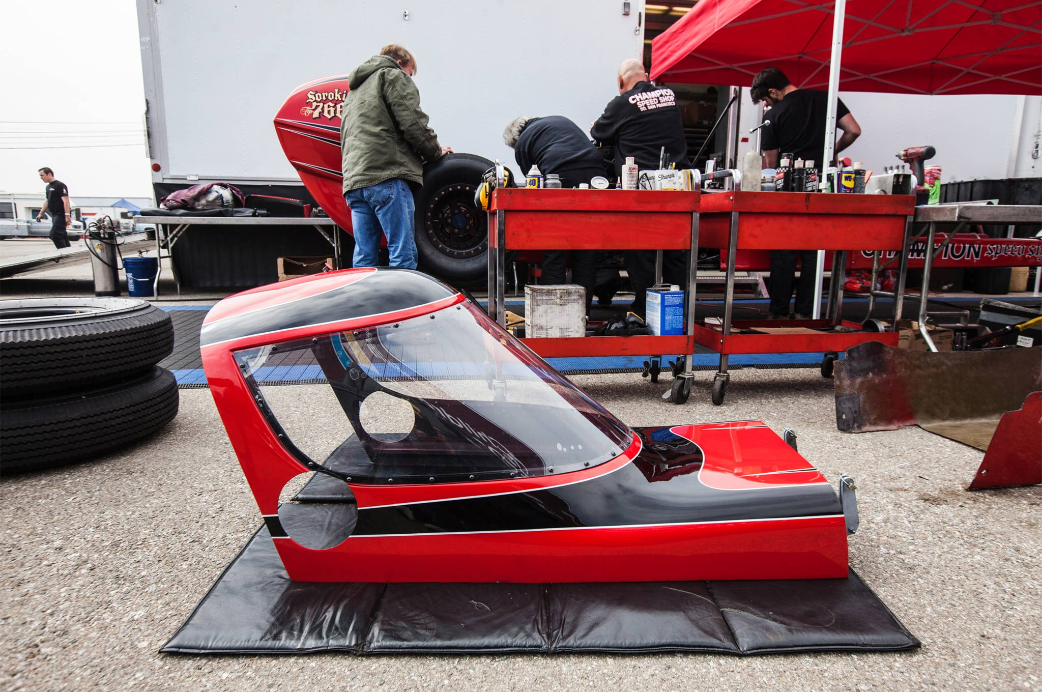 To fight the monotony of design that once relegated the dragsters to second-class status to Funny Cars, the Champion team decided to get radical with streamlining and a cockpit canopy.