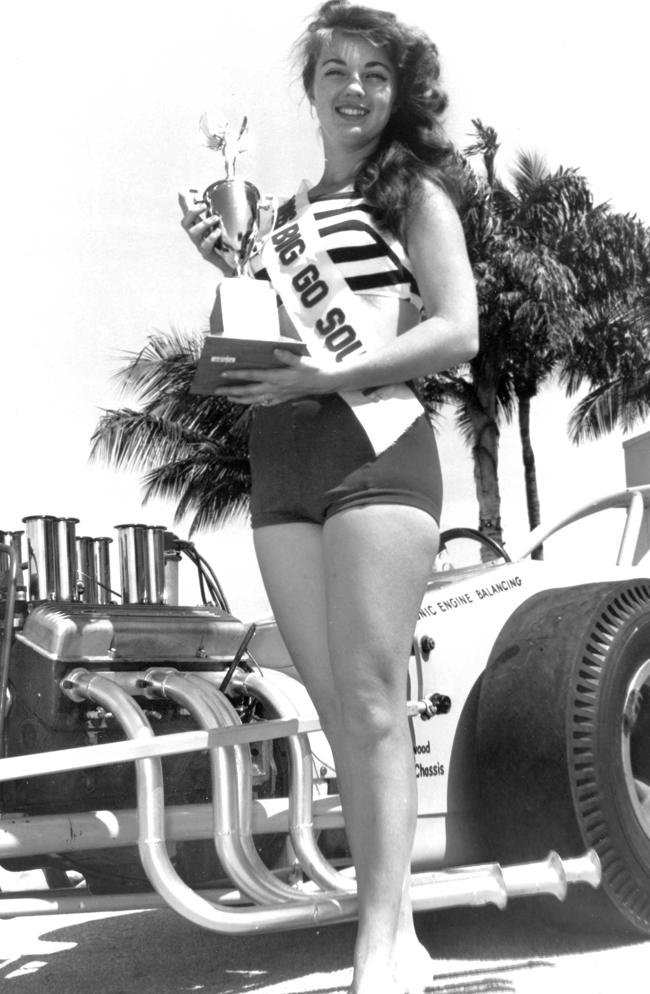 Miss Big Go South 1963 holds the gold in front of Dave Smith's North Miami-based B/Dragster. Smith went five rounds to win class at Indy in 1965 with this Lynwood Chassis car. Note long, sweeping headers and bell-ends.