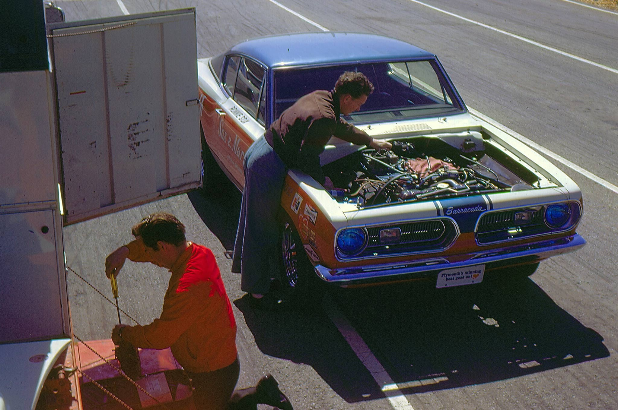 We are at Cecil County. This was the very first track test of the Sox & Martin Barracuda in late April 1968. Jake King is over the motor and Chrysler fuel-systems specialist John Bauman is setting up one of the Holleys.